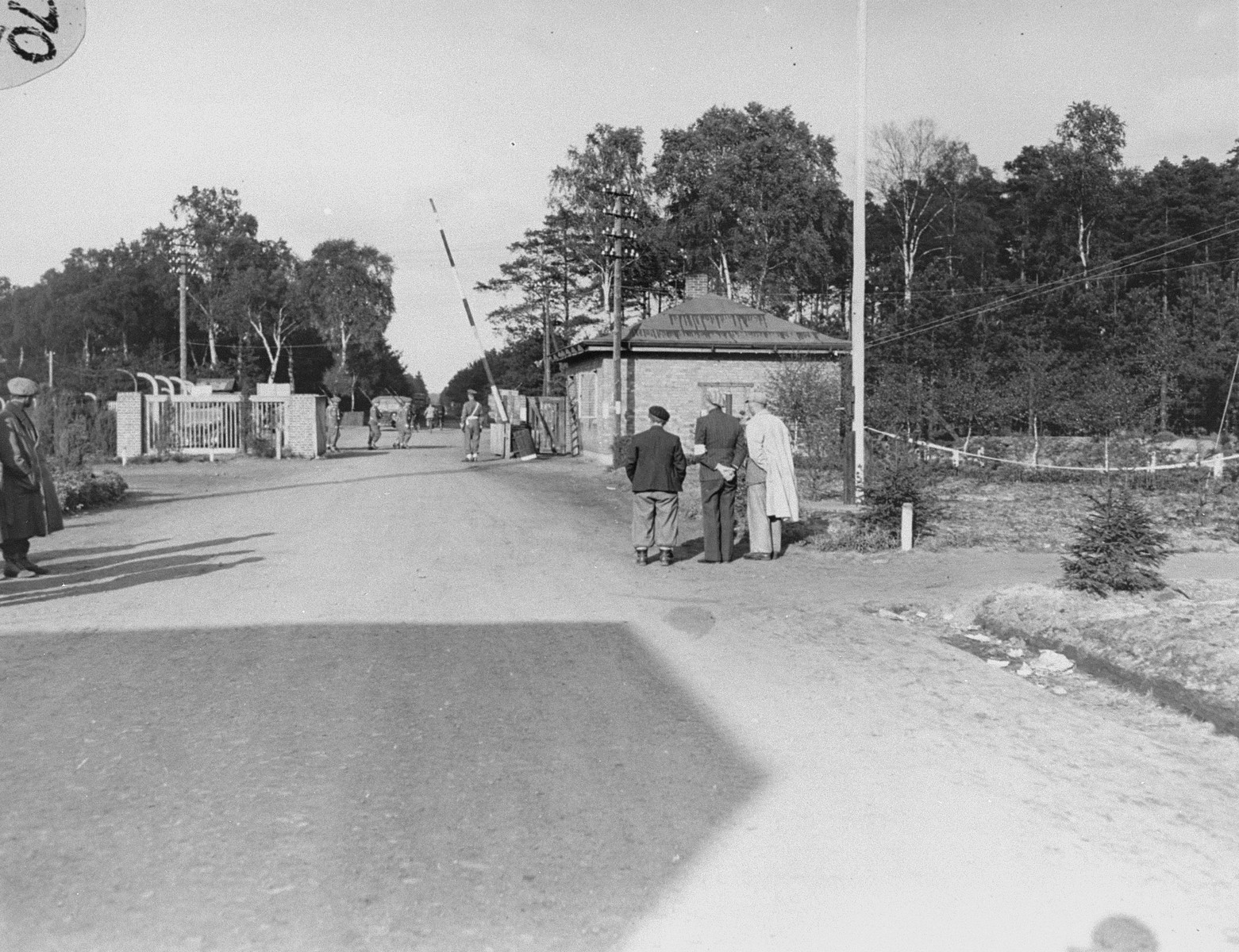 Survivors on the street in Bergen-Belsen facing the main gate to the camp.