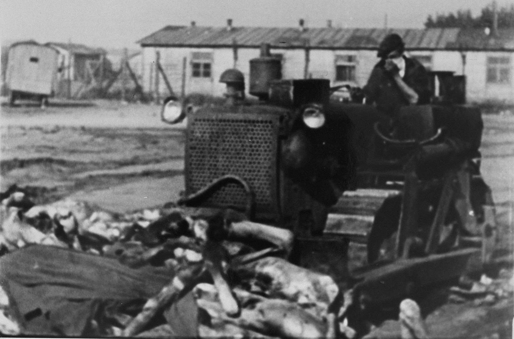 A British soldier clears corpses with a bulldozer in Bergen-Belsen concentration camp.