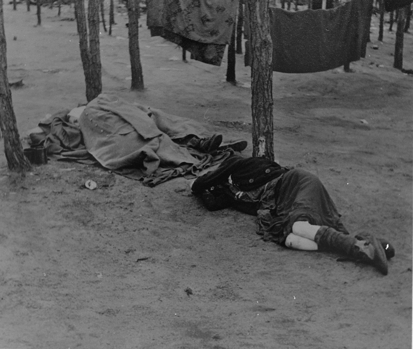 Survivors rest on the ground of Bergen-Belsen after liberation.