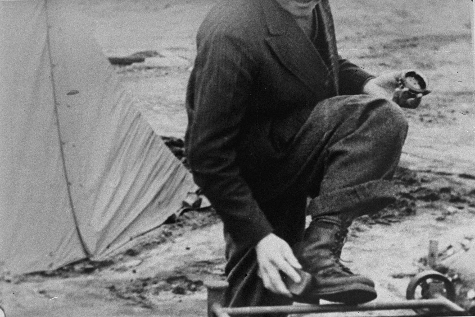 A Bergen-Belsen survivor shines his shoes outside a tent.