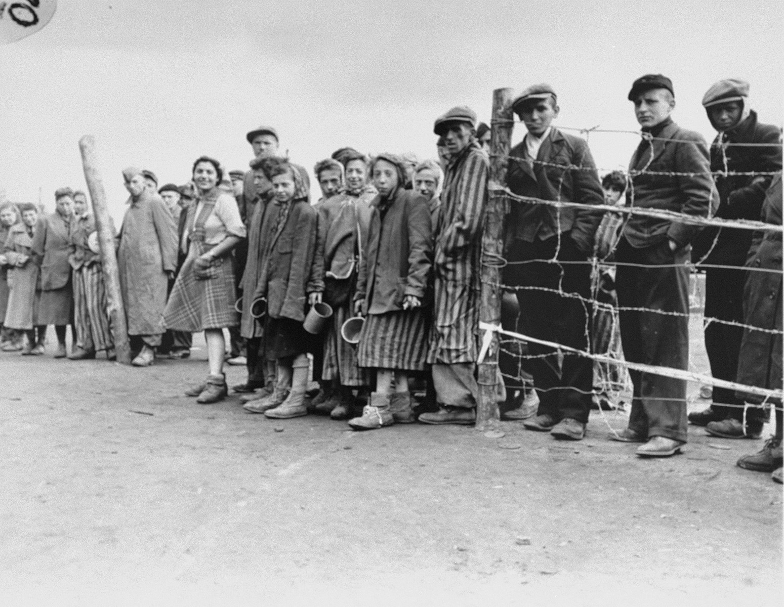 "Survivors queuing up for rations provided by the British Army.  Original caption reads:  ""Hungry internees at a former German prison camp at Belsen, Germany, wait eagerly at the cook house gate for their ration of potatoe soup."""