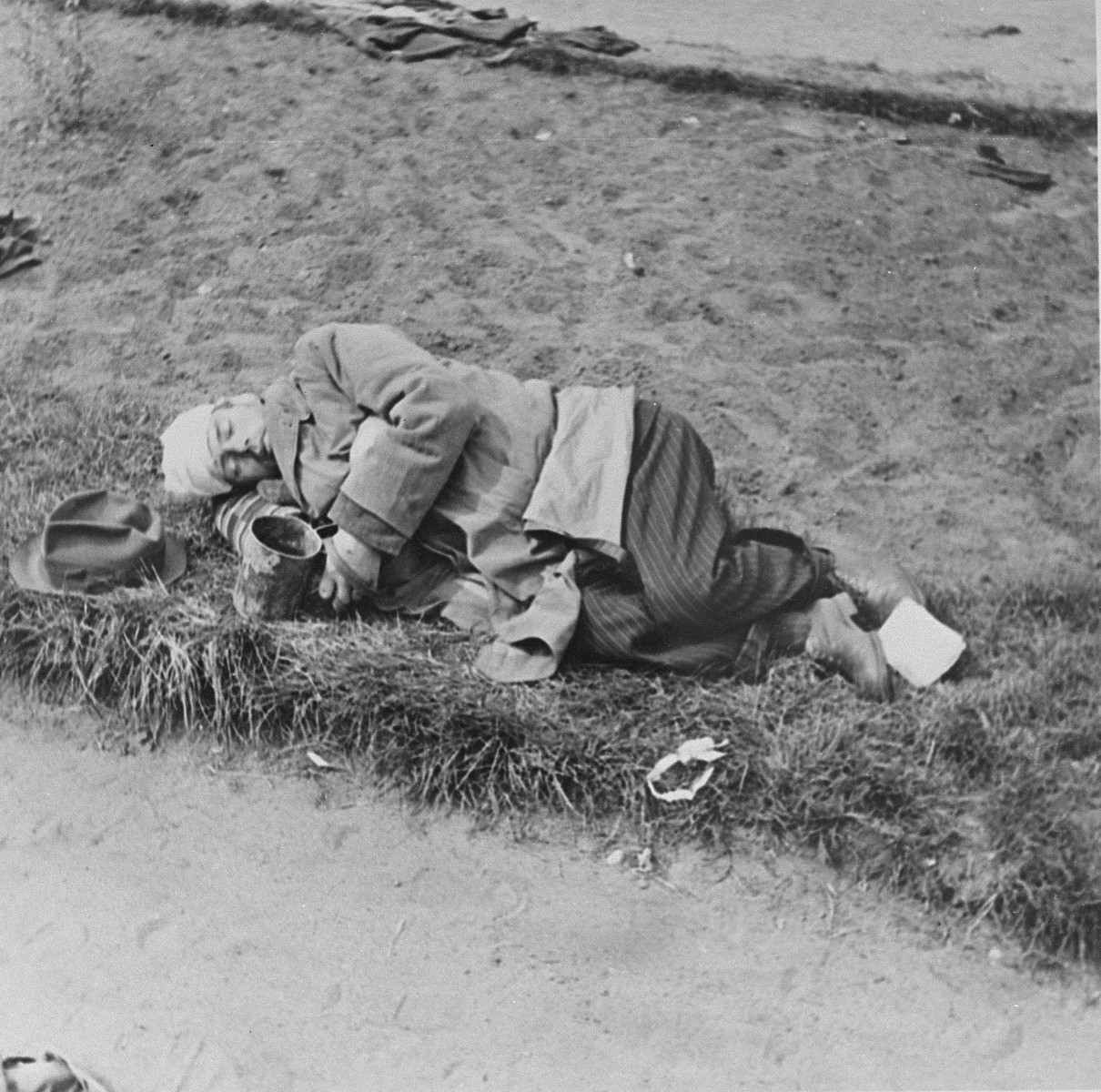 A survivor sleeps on the grounds of the Bergen-Belsen concentration camp after liberation.