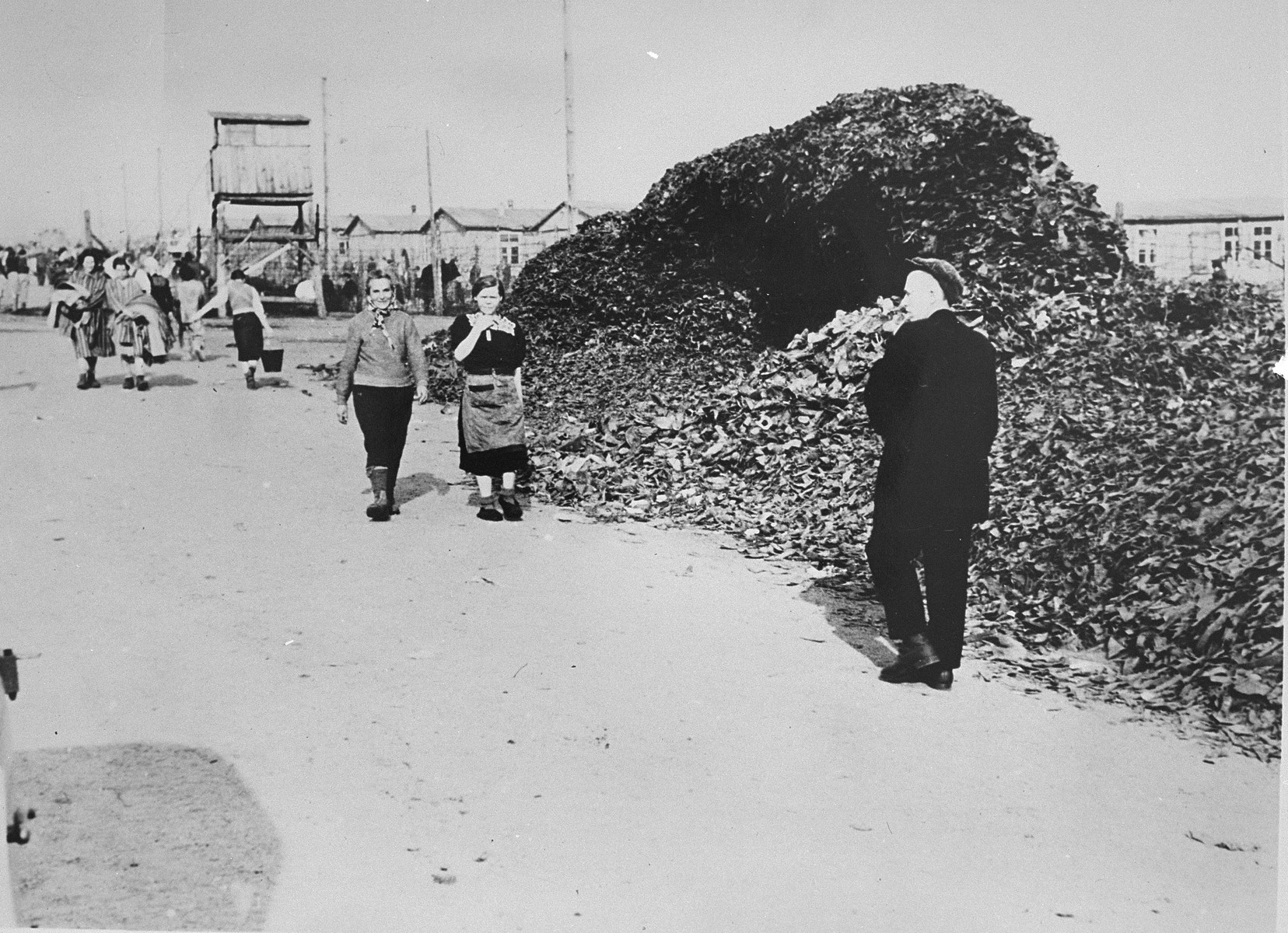 Survivors of Bergen-Belsen walk along the main street of the camp, past a pile of victims' shoes.