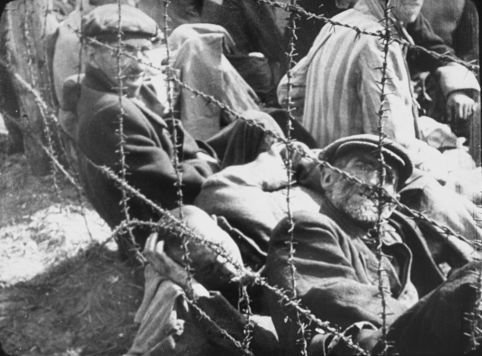 Survivors in Bergen-Belsen concentration camp rest behind a barbed wire fence after liberation.