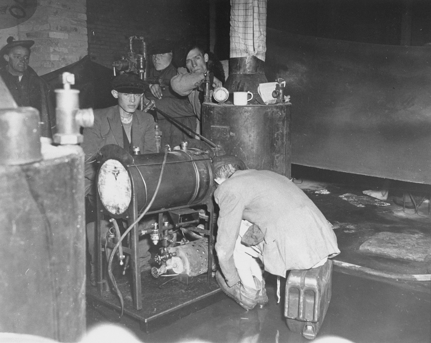 "Survivors in Bergen-Belsen warming themselves next to a water heater.  Original caption reads: "" In former German prison camp at Belsen, Germany, foreign workers attempt to warm their skeleton like bodies by a water heater.  The camp has no means of heating at all."""