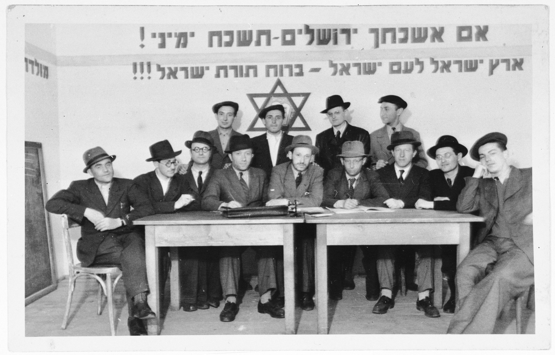 """Meeting of religious Zionists in the Zeilsheim displaced persons' camp.  The signs on the wall read, """"If I forget thee O Jerusalem, may my right arm be forgotten"""" and """"The land of Israel for the people of Israel""""."""
