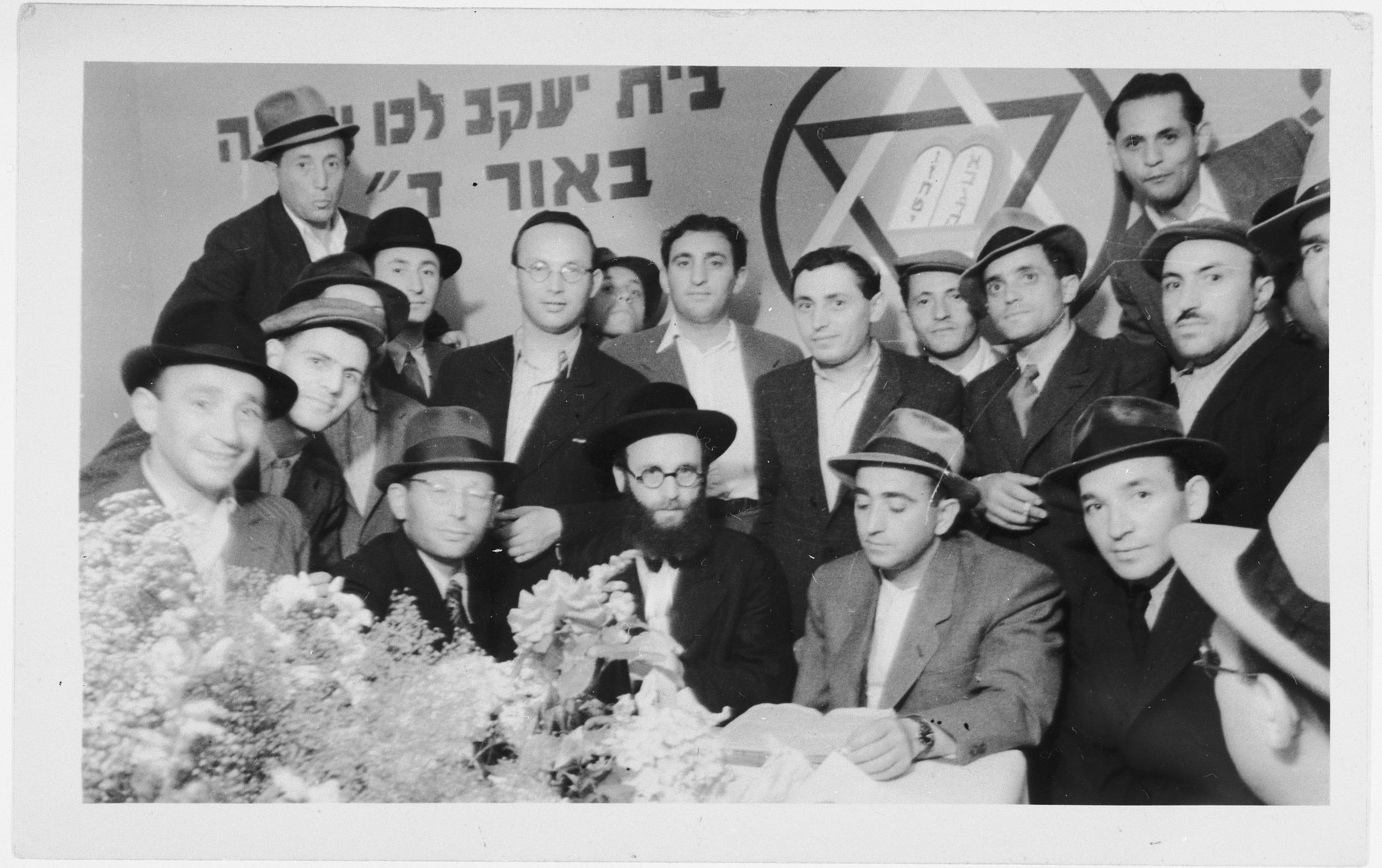 "Religious Zionists in the Zeilsheim displaced persons' campgather in front of a banner proclaiming that ""the House of Jacob, arise and go"" ."