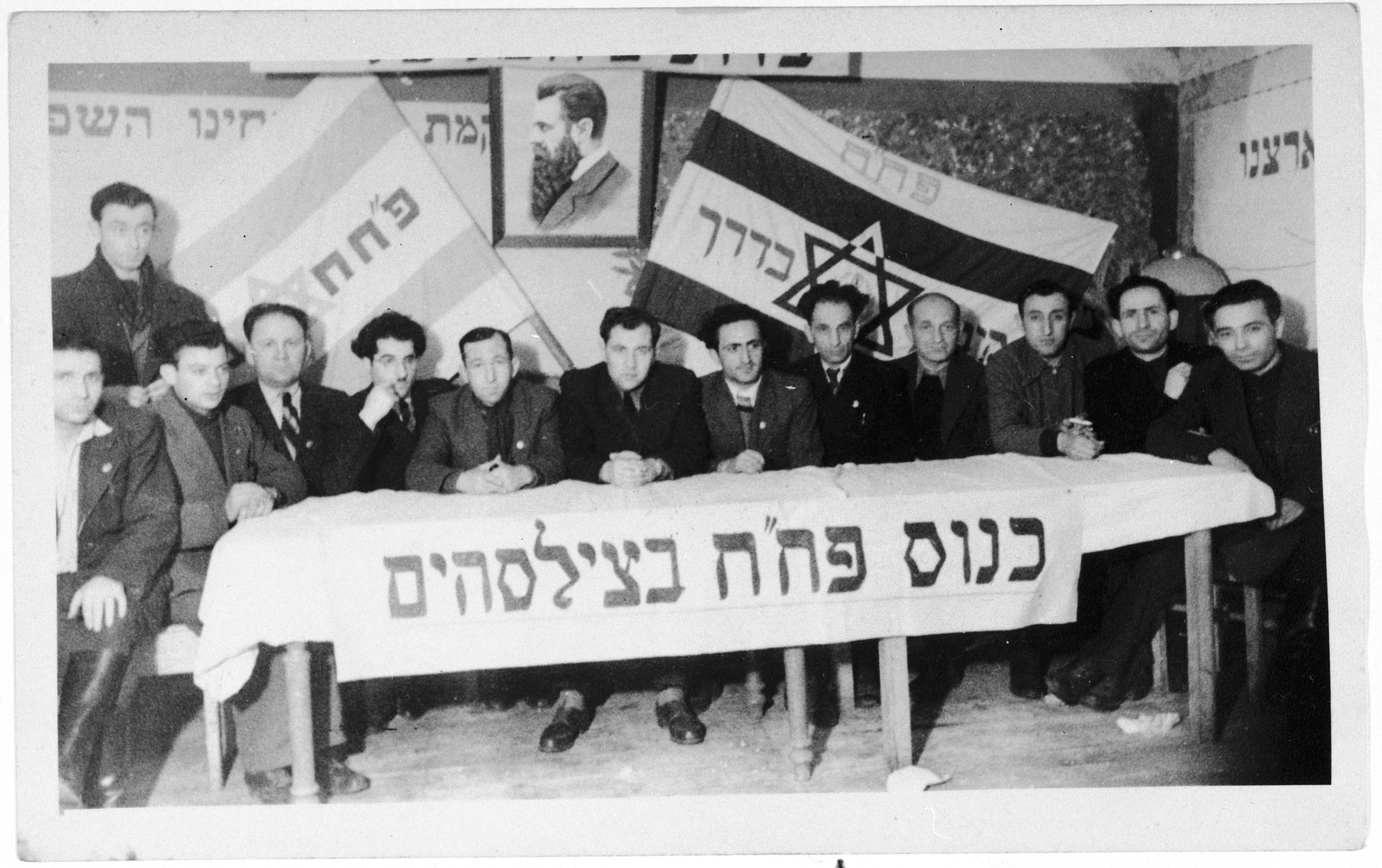 Members of the Zionist group Partizanim-Hayyalim-Halutzim meet in the Zeilsheim displaced persons' camp held in a room decorated with flags and posters.