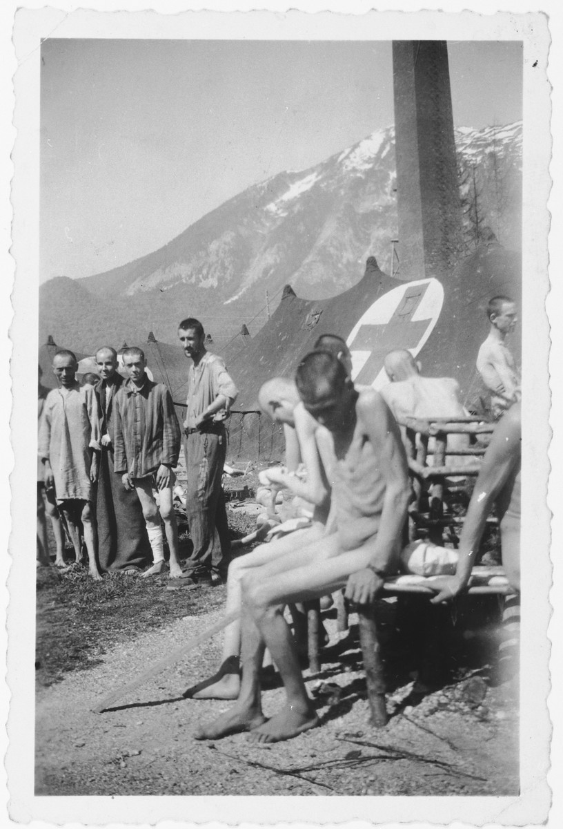 A group of survivors waits outside the Red Cross tent in Ebensee .