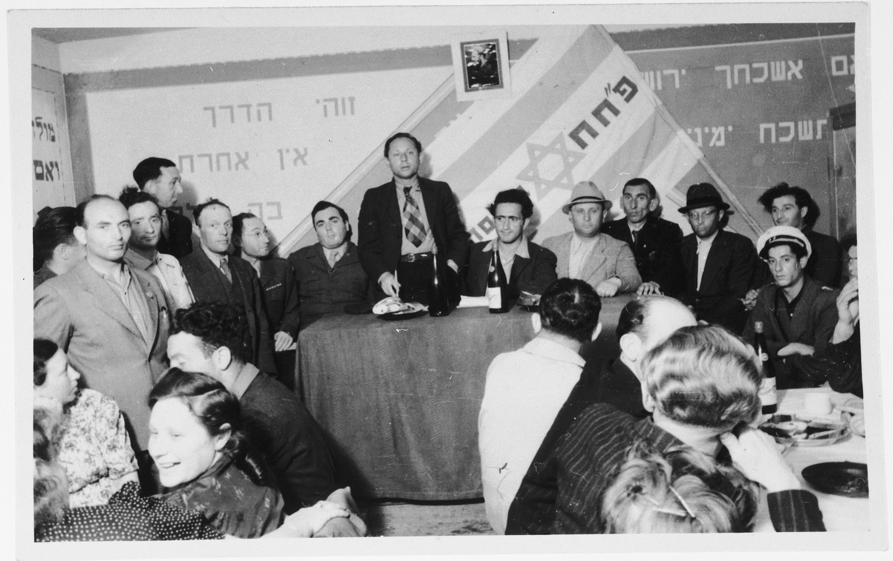 Members of the Zionist group Partizanim-Hayyalim-Halutzim meet in the Zeilsheim displaced persons' camp held in a room decorated with a flag and posters.