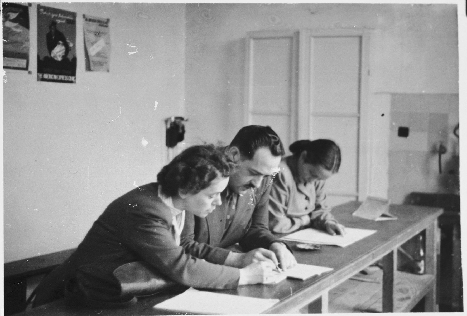 Representatives of the Canadian government who helped facilitate the immigration of displaced persons to Canada prepare to send telegrams.  Pictured from left to right are Margot Baignee, a Catholic who helped trade test prospective immigrants, Lucien St. Cyr, a representative of the Labor Department, and Bella Meiskin, an unofficial member of the delegation who worked for the Jewish Labor Committee.