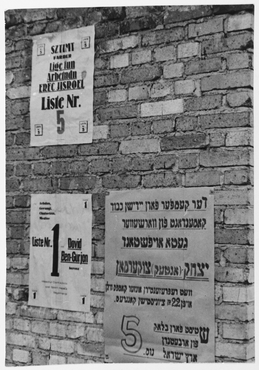 Election posters on a wall in the Zeilsheim displaced persons' camp.  List one is headed by David Ben-Gurion and list five by Antek Zuckerman.