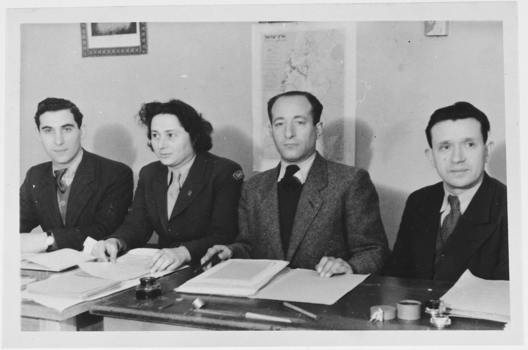 A female JDC aid worker and three men pose behind their desks in front of a map of Israel in the Zeilsheim displaced persons' camp.