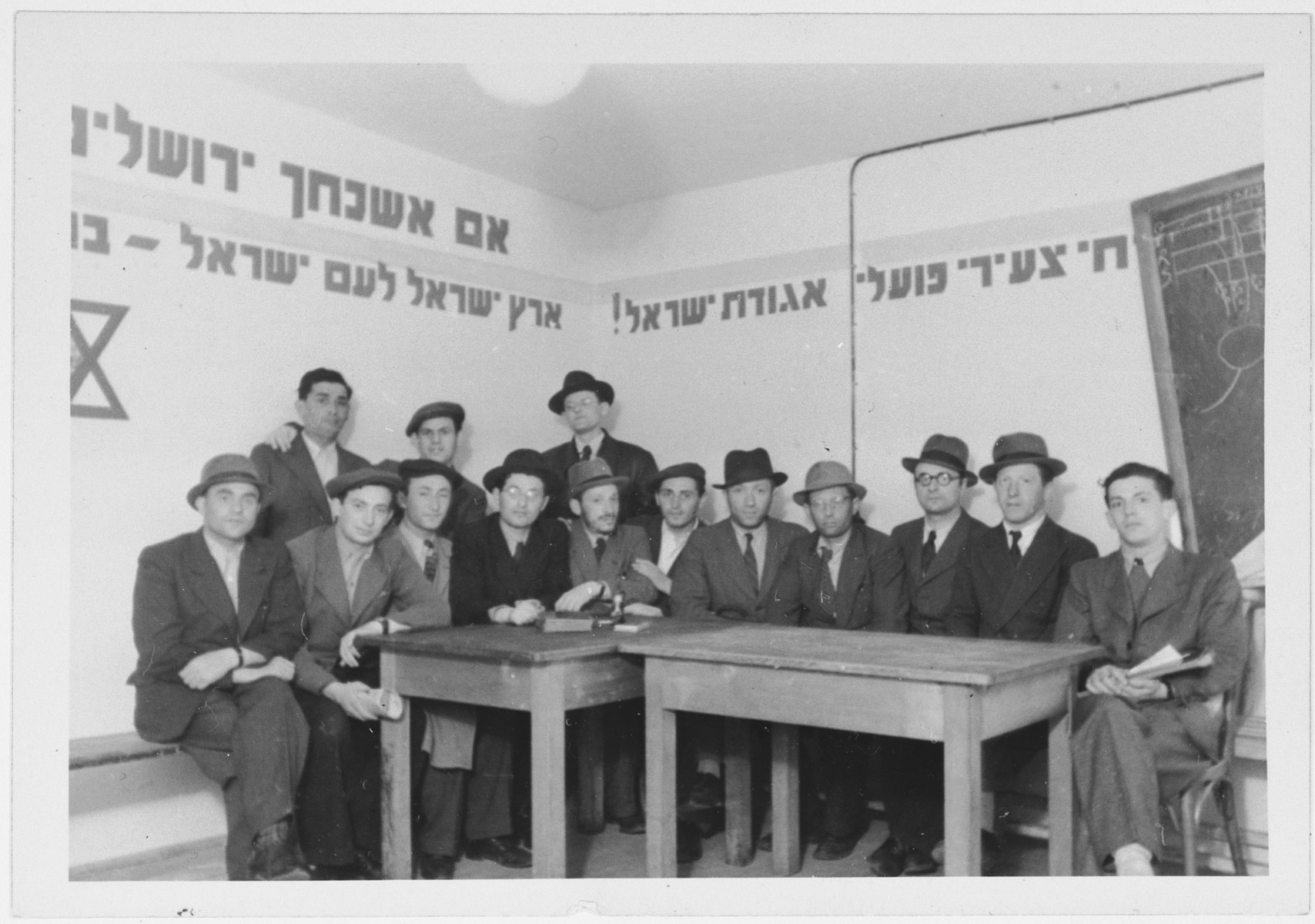 "Meeting of religious Zionists in the Zeilsheim displaced persons' camp.  The walls are decorated with sayings including ""If I forget thee O Jerusalem"" and ""the Land of Israel for the People of Israel""."
