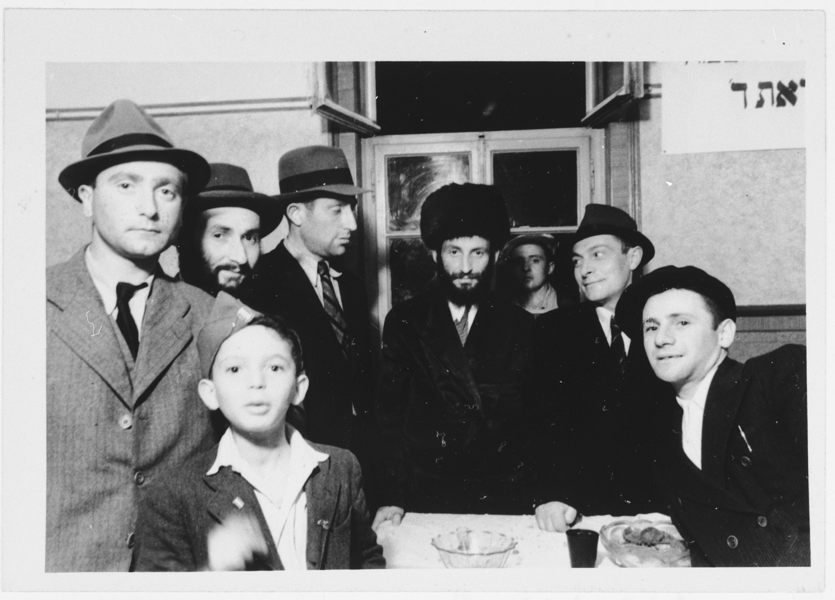 Group portrait of Orthodox men and a young boy standing next to a table in the Zeilsheim displaced persons' camp.