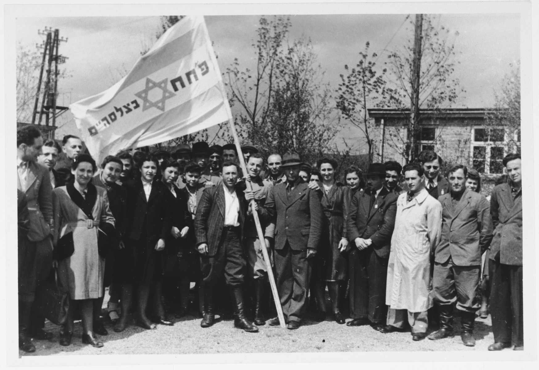 Members of the PHH (Partizanim-Hayyalim-Halutzim) gather alongside their banner in the Zeilsheim displaced persons' camp.