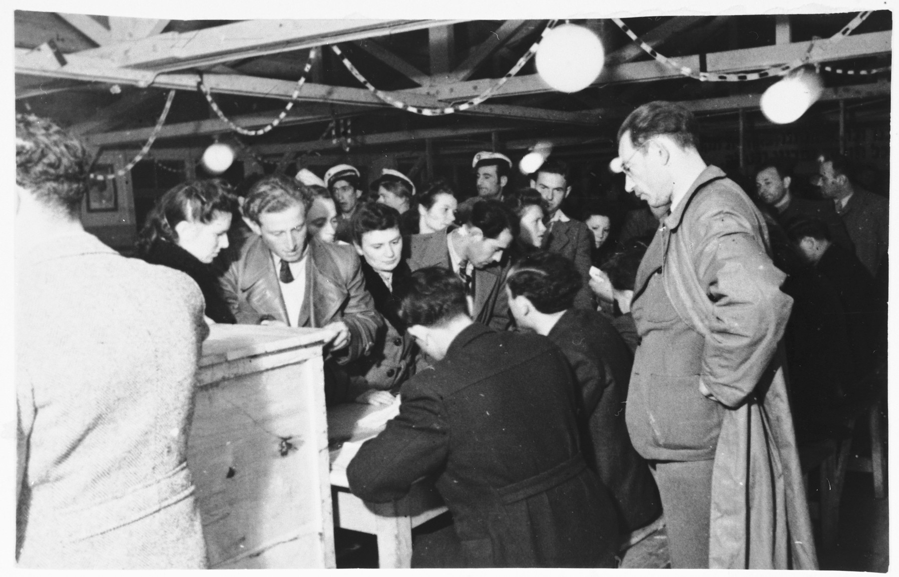 Men and women file past a table to vote in elections in the Zeilsheim displaced persons' camp.  Among those pictured is Abraham Poznanski, in the center of the photo, looking down at the table, in profile.  His wife, Hanka (Anna) Poznanski is standing behind him, looking off to the right.