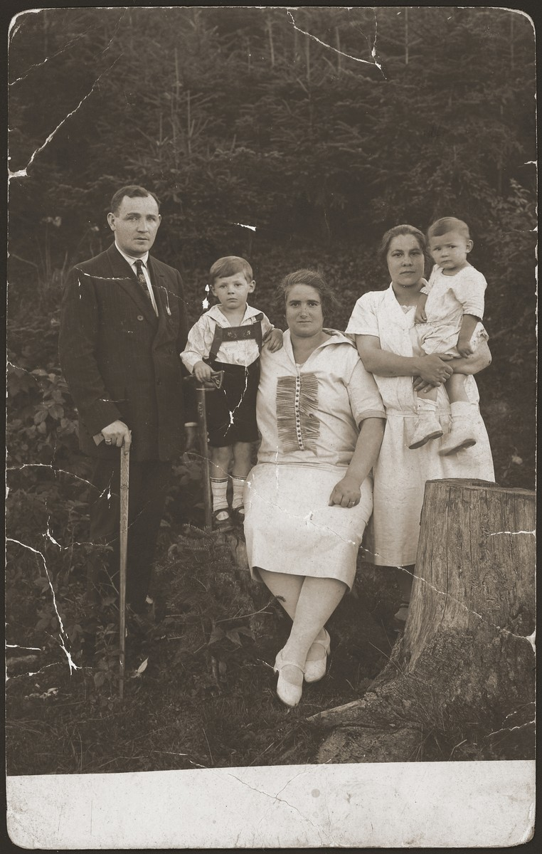 A Jewish family from Rabka, Poland poses outside during an excursion.    Pictured from left to right are: Henry Seitler (Roman's father), Iziek Seitler (Roman's brother), Lea Seitler (Roman's mother), and the maid holding Roman.  Roman was the sole survivor of his family.