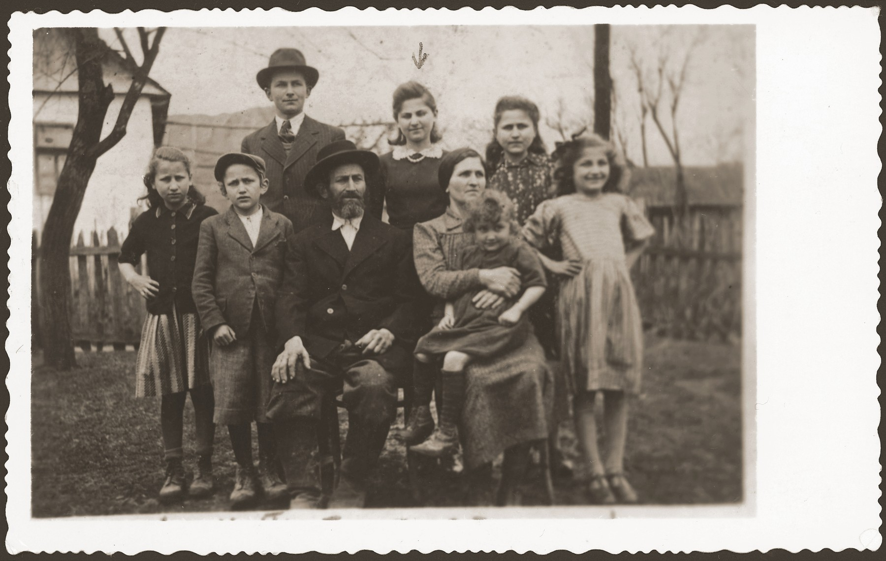 Group portrait of members of a Jewish family in the yard of their home in Volovec.    Pictured are members of the Kreisman family.  Frida Kreisman is in the back row, center.