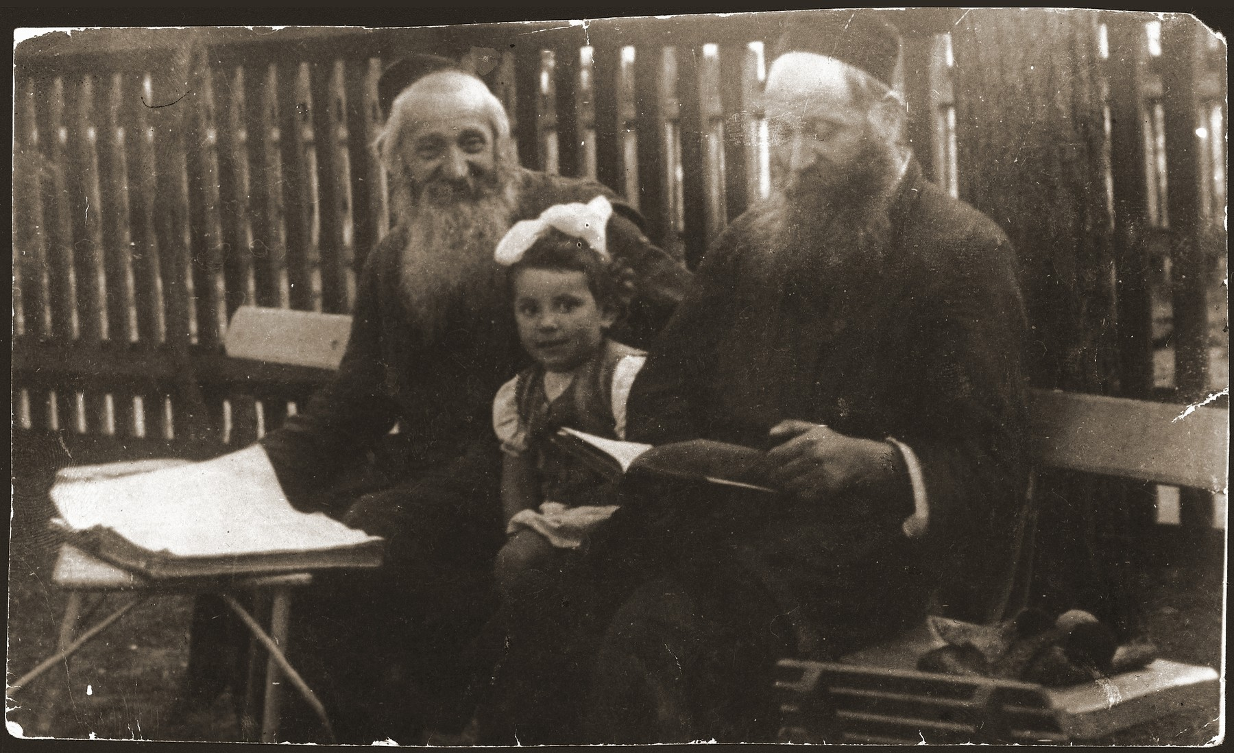 Two kosher slaughterers in Otwock study a page of the Talmud together.  Pictured are the brothers, Chaim (left) and Herschel (right) Froman.  Between them is Chaim's daughter Bella (the wife of the donor).