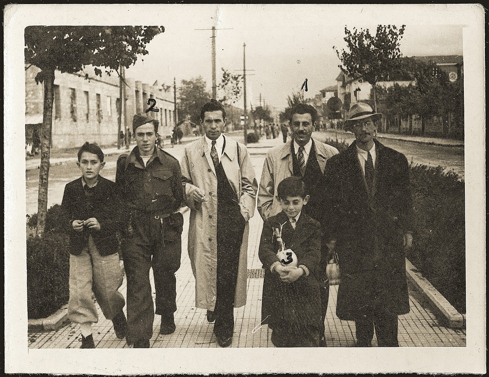 Mosa (Moshe) Mandil, Gavra, and Refik Veseli walk along the streets of Tirana with friends on liberation day.  In 1990 Refik Veseli was recognized by Yad Vashem as one of the Righteous Among the Nations.  Mosa is pictured second from the right, Gavra walks ahead of him, Michael Komforti is on the far left and Refik is second from the left.