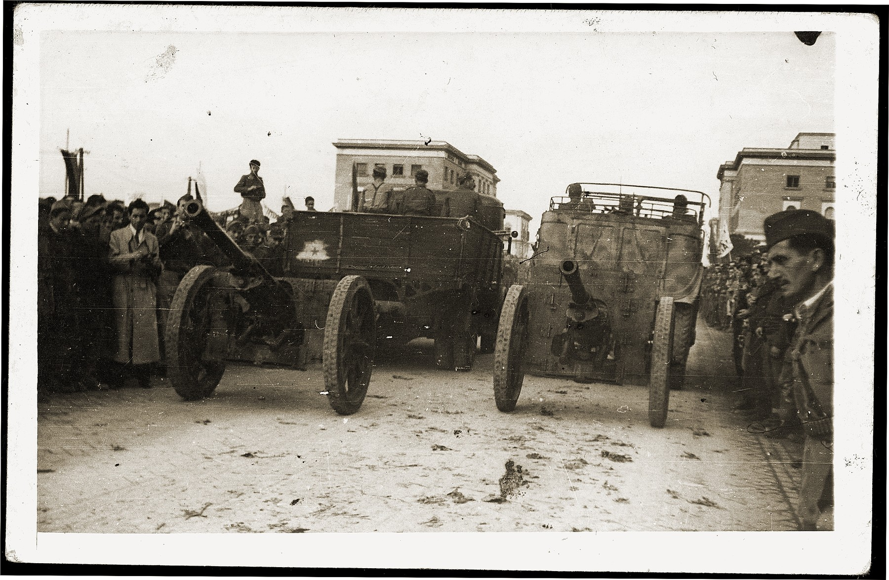 Albanians view two cannons being towed by trucks during a military parade marking the liberation of Tirana.