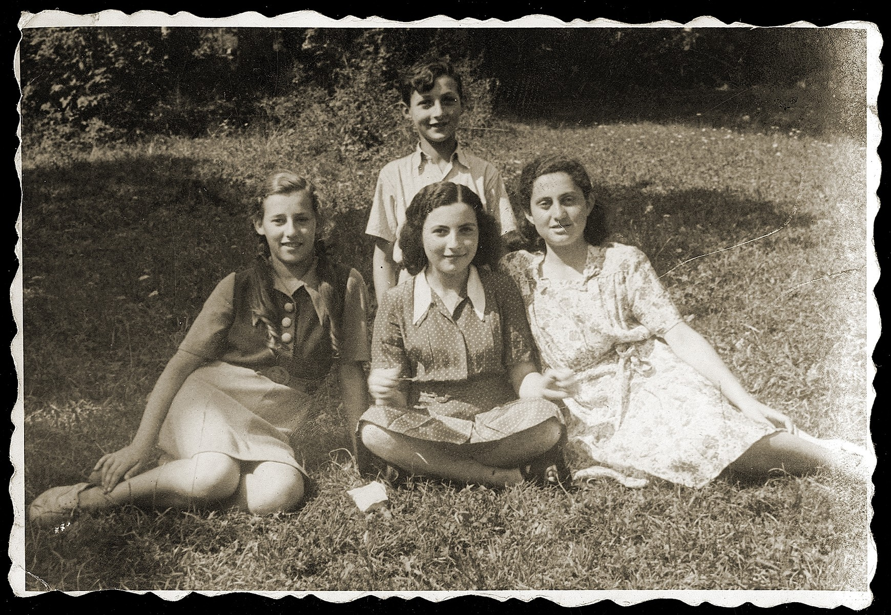 Four Jewish youth who returned to Bedzin after the war, pose outside seated on the grass.  Among those pictured are Lolek Przyrowski (top) and Shulamit Sternfeld (right).