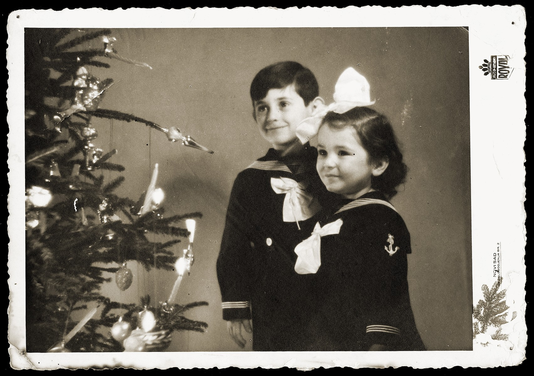 Gavra and Irena Mandil pose next to a Christmas tree.  Mosa (Moshe) Mandil often used his children as models to advertise his photo studio.    This photograph, which he took in the fall of 1940 to promote business for the upcoming Christmas season, later saved the lives of his family.  During their escape from Serbia by train in April 1941, the Mandils were stopped by German SS, who demanded to see their papers.  When the Germans accused them of being Jews, Mosa showed them this photo, and the family was left alone.