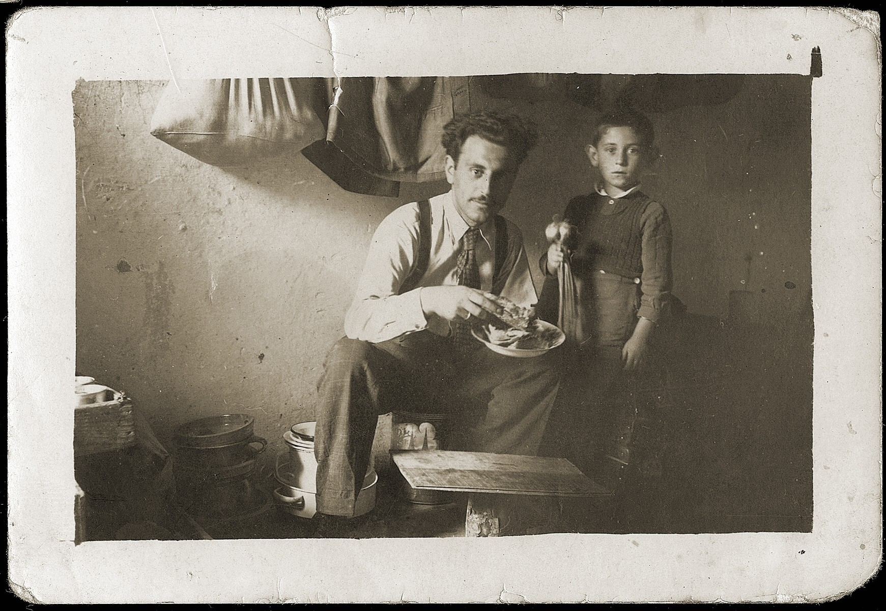 Mosa Mandil, a Jewish refugee from Serbia, poses with his son Gavra in the prison cell in which they are living in Italian-occupied Pristina.