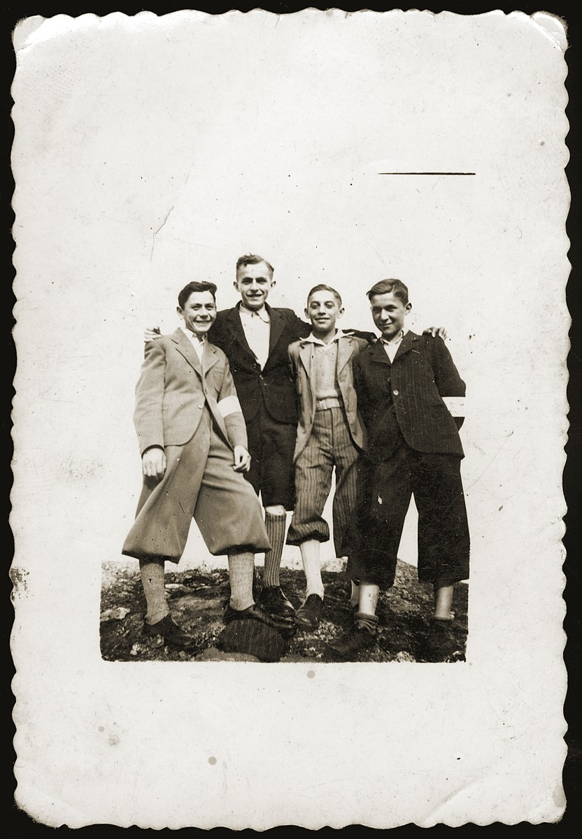 Portrait of four youths in the Dabrowa ghetto wearing armbands.  Motek Aberfeld stands second from the left.