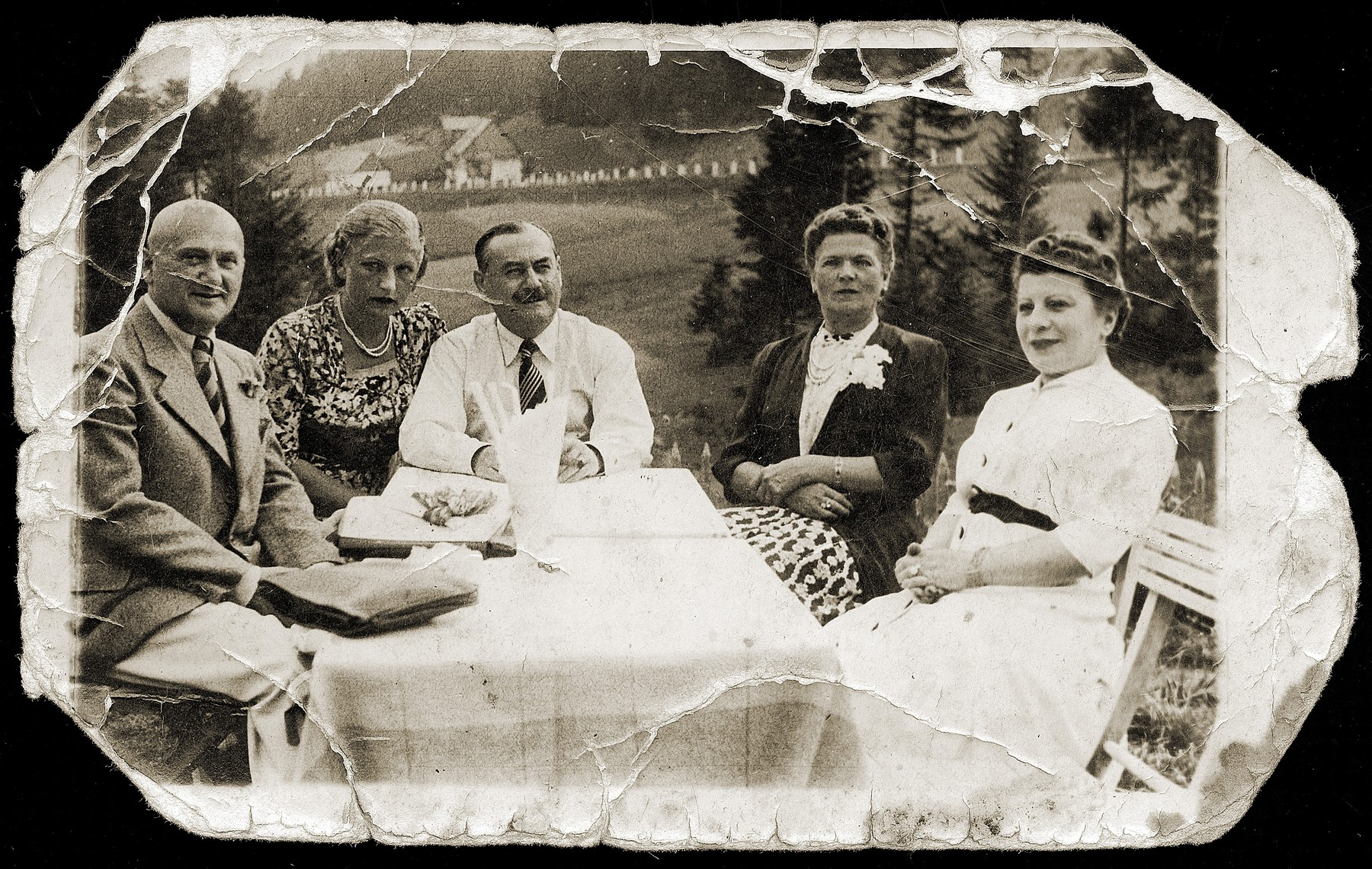 A group of friends sit outside around a table.  Pictured from left to right are: ? Pinkus, unknown, Simon Furstenberg, Helena (Goldminc) Furstenberg and Mania Pinkus.