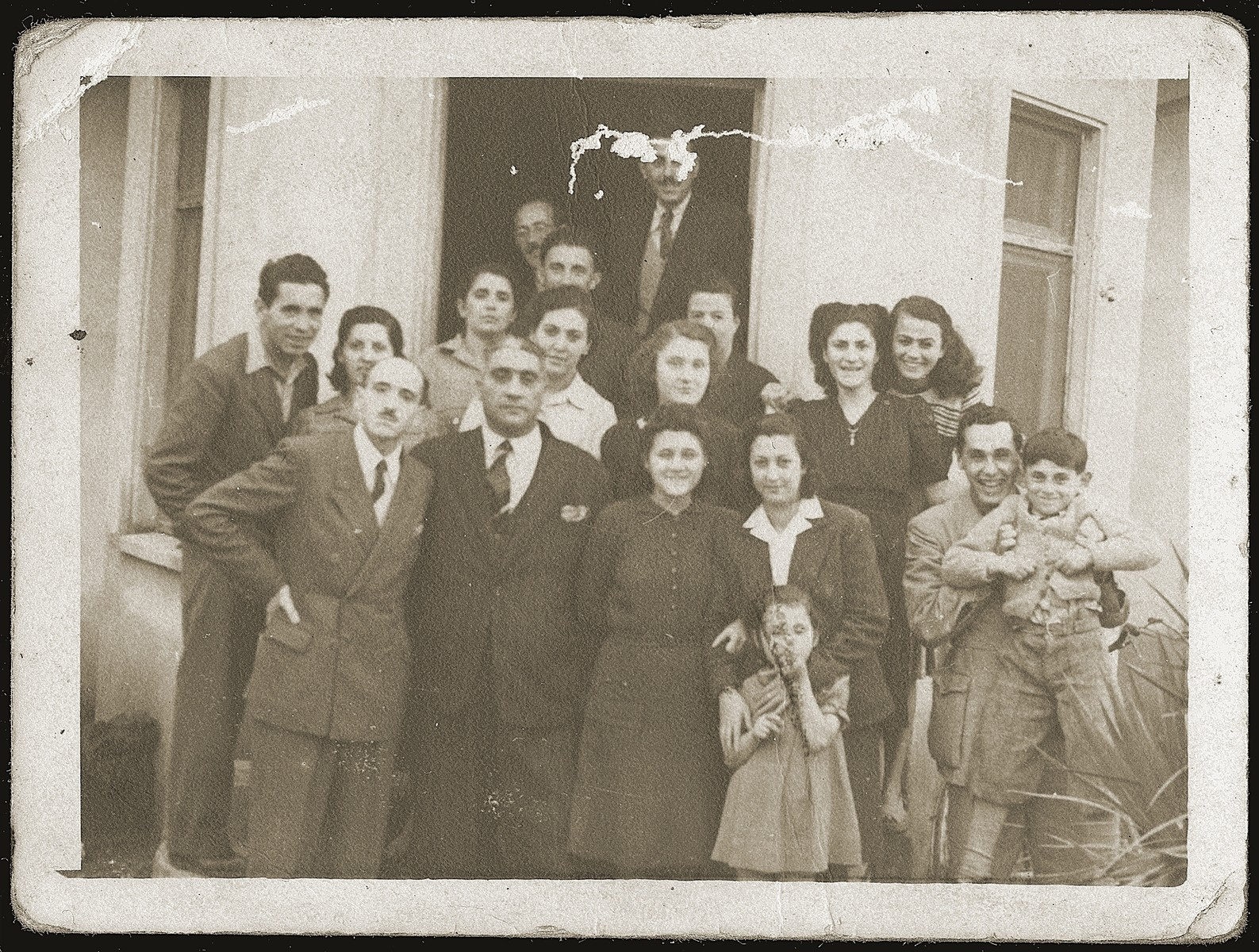 Group portrait of Jewish refugees in front of the home of Neshed Ismail in Tirana after the liberation.    Pictured are Mosa (Moshe) Mandil (top, in the doorway), Gabriela Mandil (center, middle row),Irena (front) and Gavra Mandil (at the far right) and Neshed Ismail (far left).  Also pictured are Mr. and Mrs Ruchvarger; Mr. and Mrs. Sabitai Gershon and their daughter Stella; Yosef, Finitza and Rozica Ben-Yosif; and Mr. and Mrs. Naftali Komforti