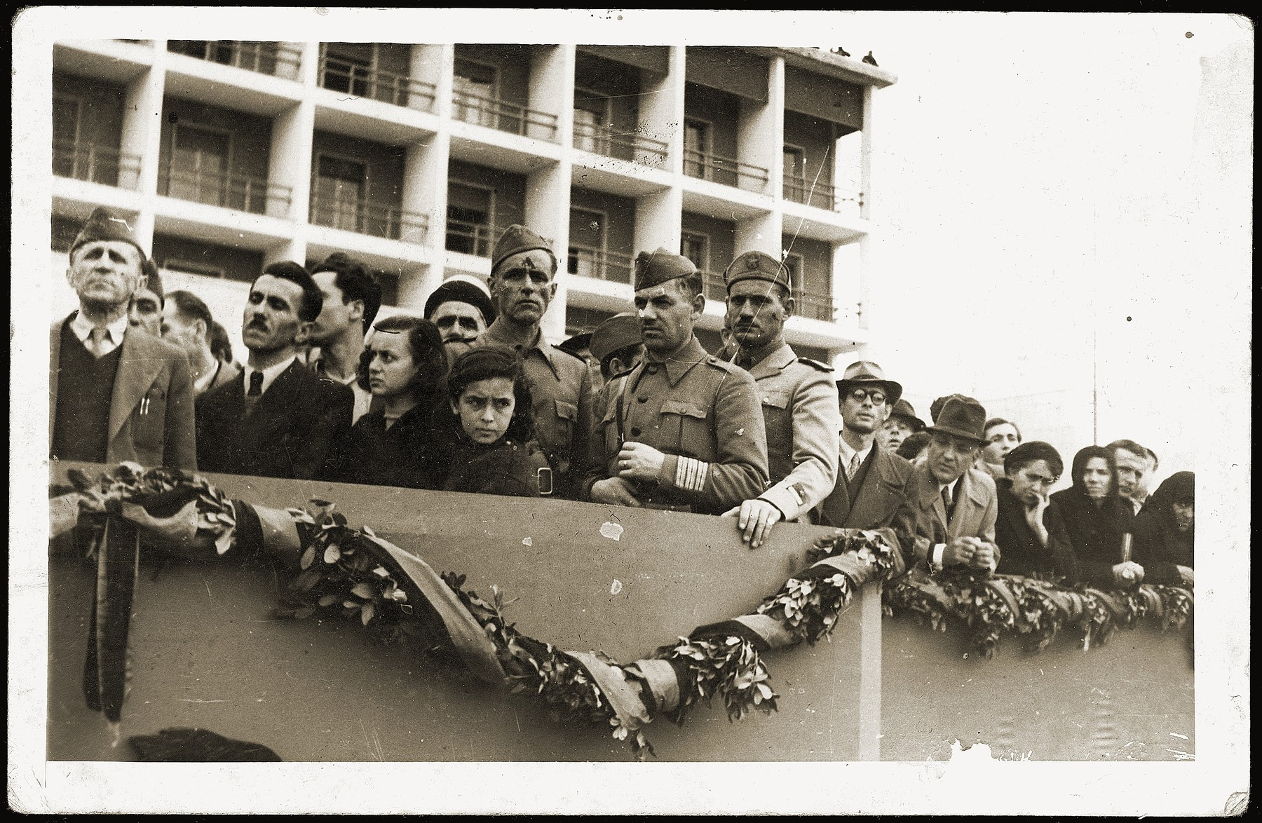 Albanian soldiers and civilians watching a military parade marking the liberation of Tirana.