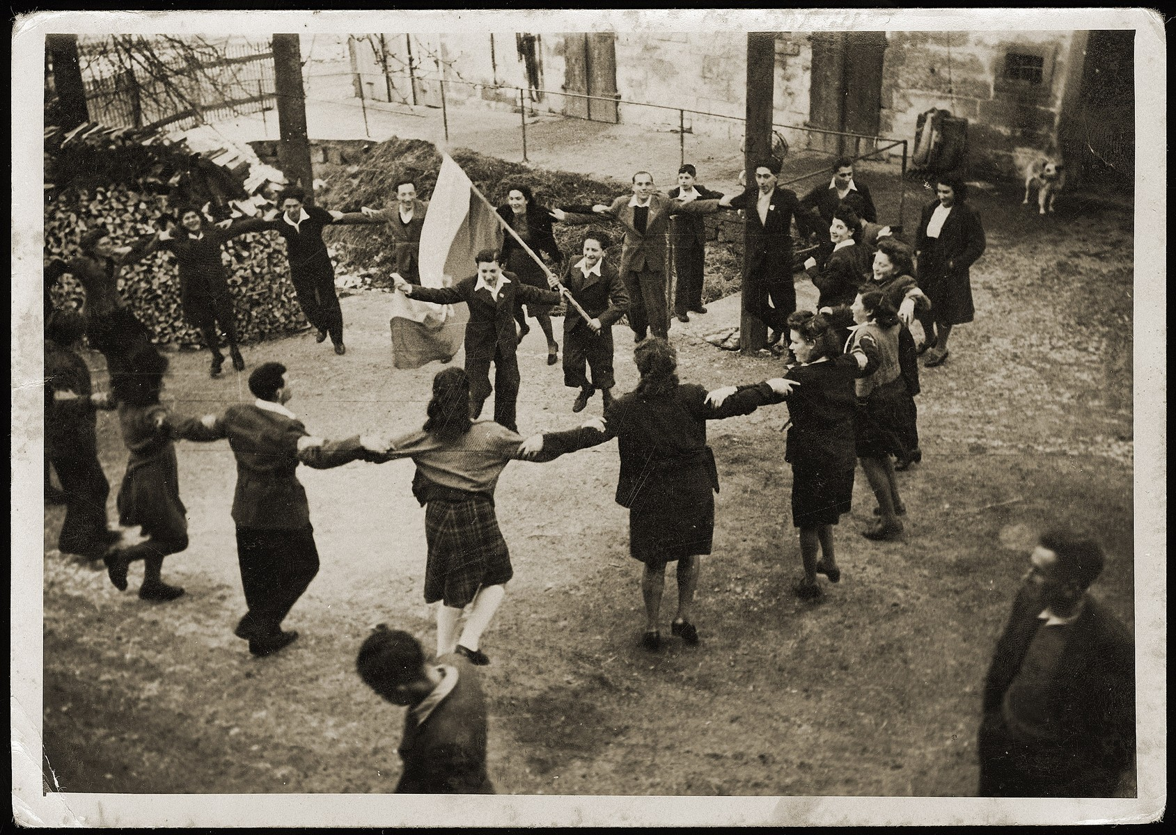 Zionist youth dance the hora around a flag [perhaps prior to their leaving for Palestine aboard the Champollion].