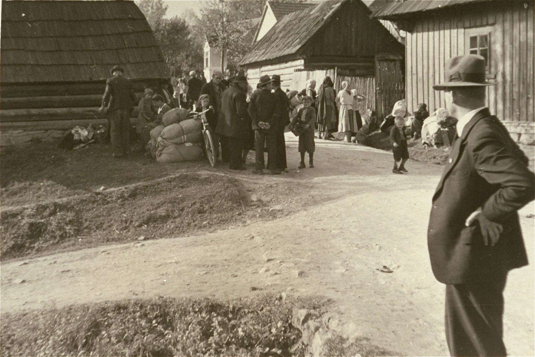 [Probably, Poles gathered outside their homes during a resettlement action.]    One of twenty-six images of Einsatzgruppen activities in Poland in 1939, found by Joseph Igra after the war, in a an album in an apartment in Sosnowiec.