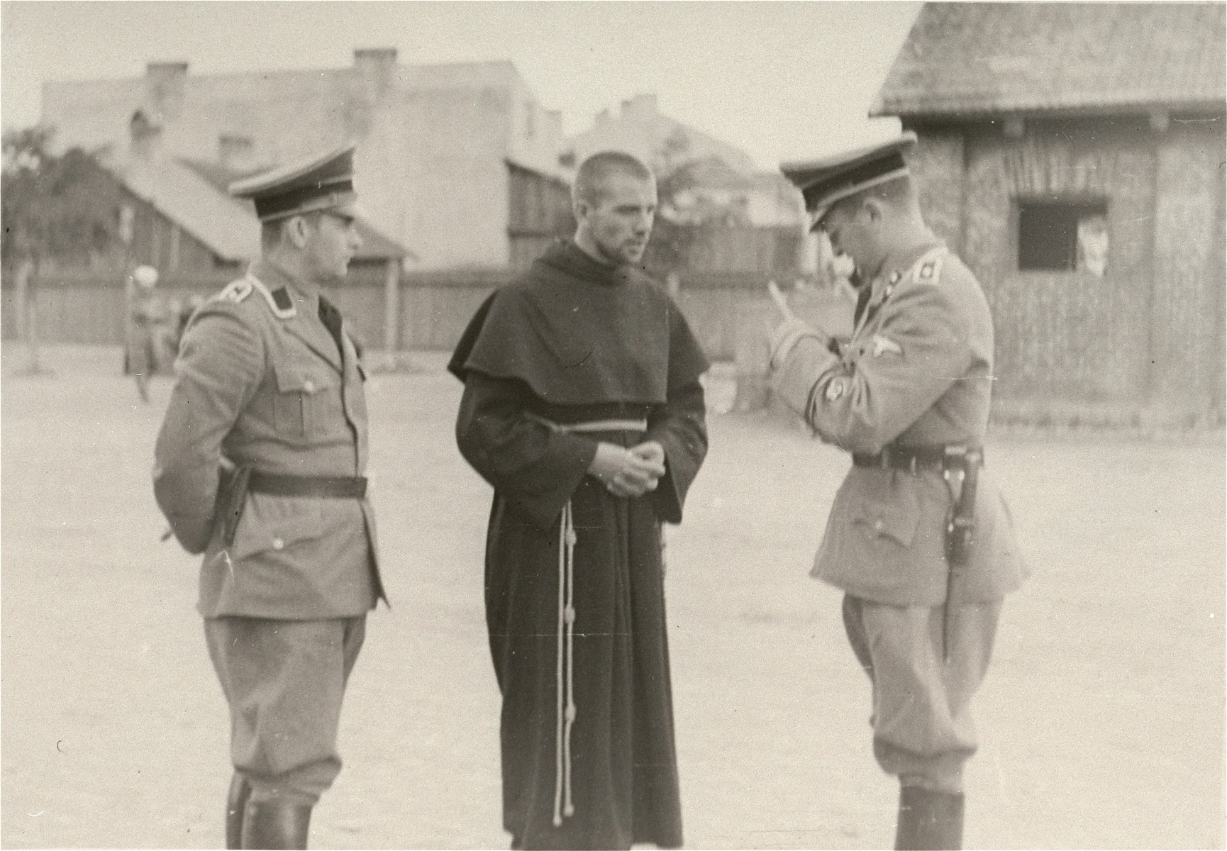 [Probably, two SD officers questioning a Polish cleric.]   One of twenty-six images of Einsatzgruppen activities in Poland in 1939, found by Joseph Igra after the war, in a an album in an apartment in Sosnowiec.