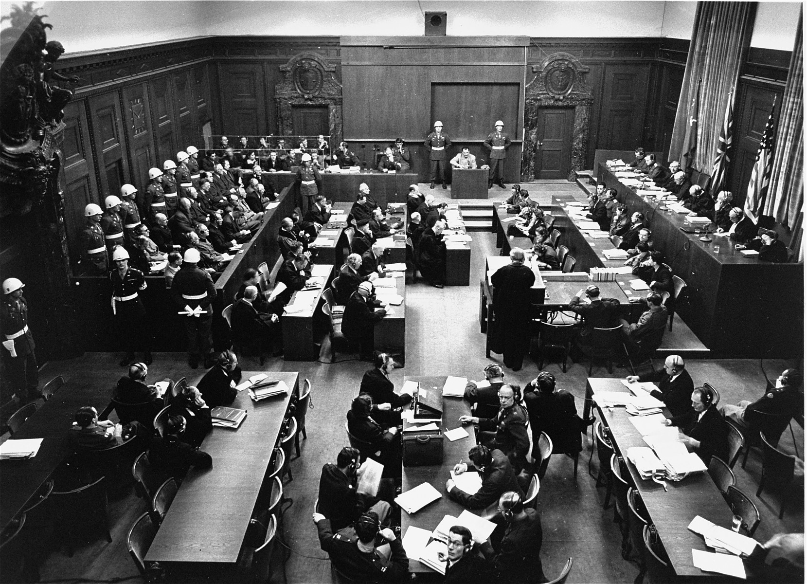 View of the packed courtroom of the International Military Tribunal at Nuremberg.  Lawyers for the prosecution are at the bottom, the defendants on the left, and judges on the right.