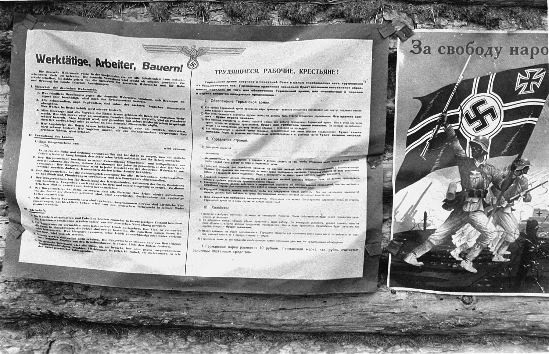A bilingual notice posted by German authorities shortly after the start of the German occupation.  It outlines measures the army will take for the security of German troops, as well as German plans for the administration of conquered territory.  The propaganda poster on the right shows victory German troops freeing the USSR.