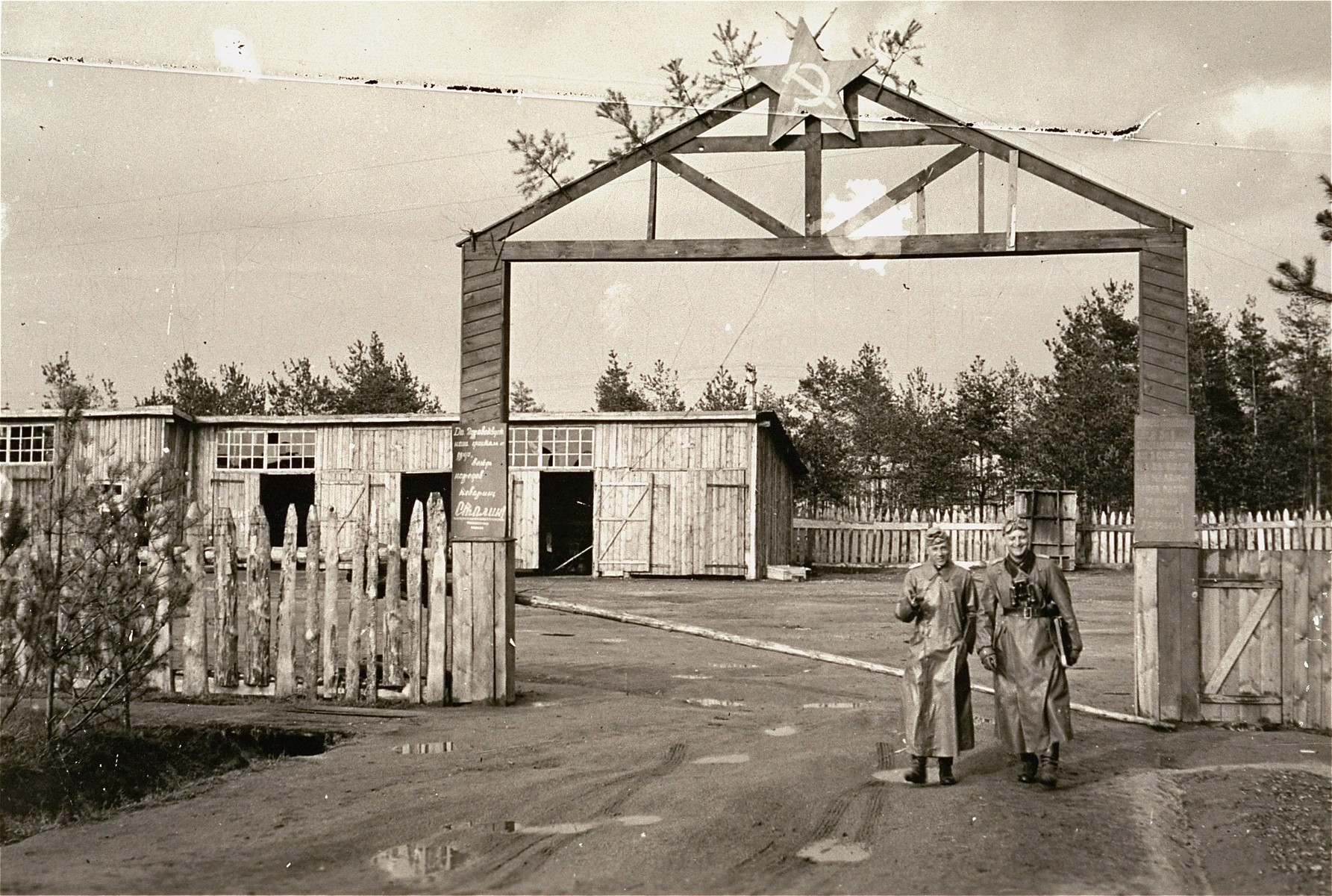 Two German soldiers stand outside of the gate of an abandoned Soviet camp.