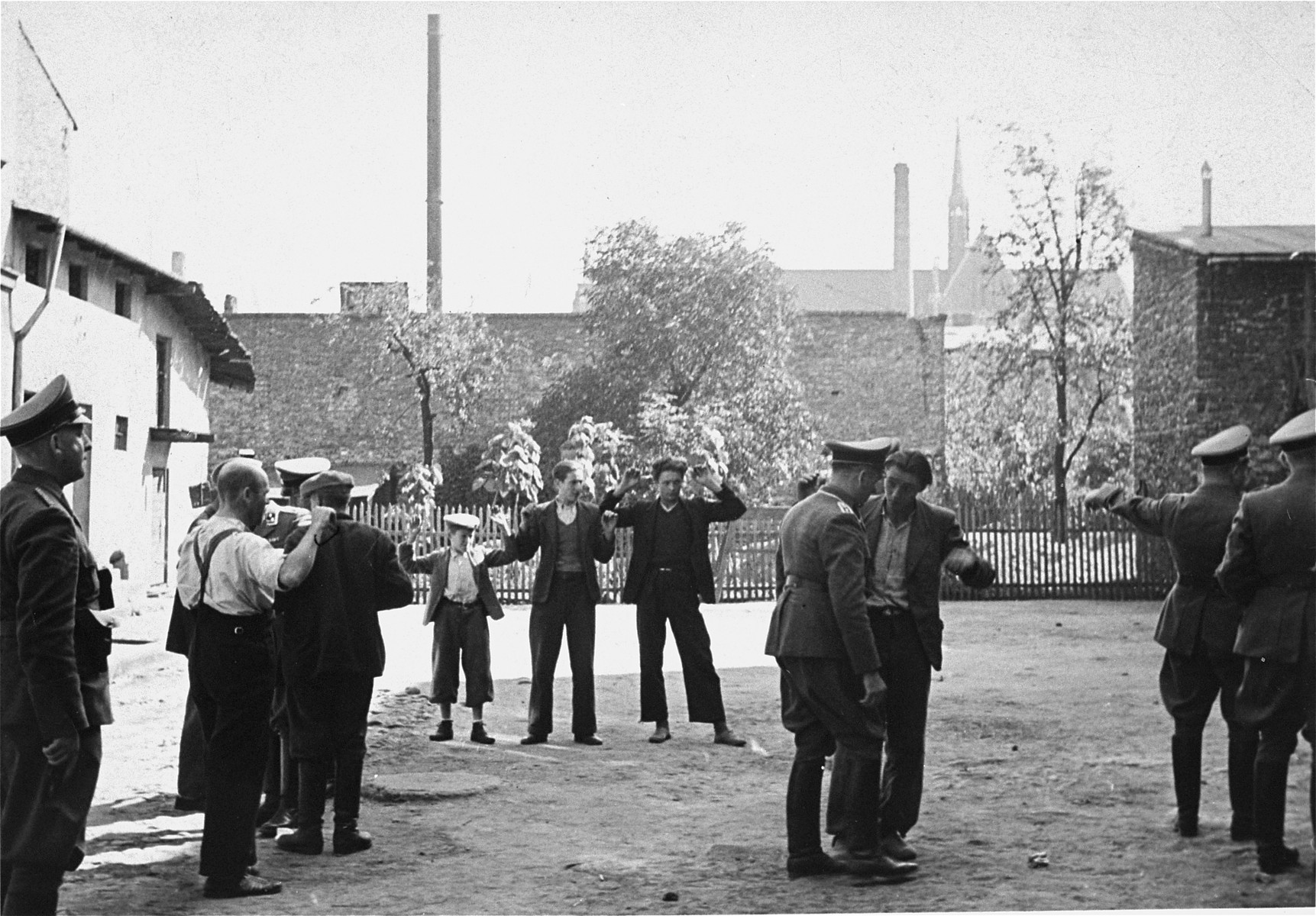 [Probably, SD officers questioning a group of Poles they have detained on the street.]   One of twenty-six images of Einsatzgruppen activities in Poland in 1939, found by Joseph Igra after the war, in a an album in an apartment in Sosnowiec.
