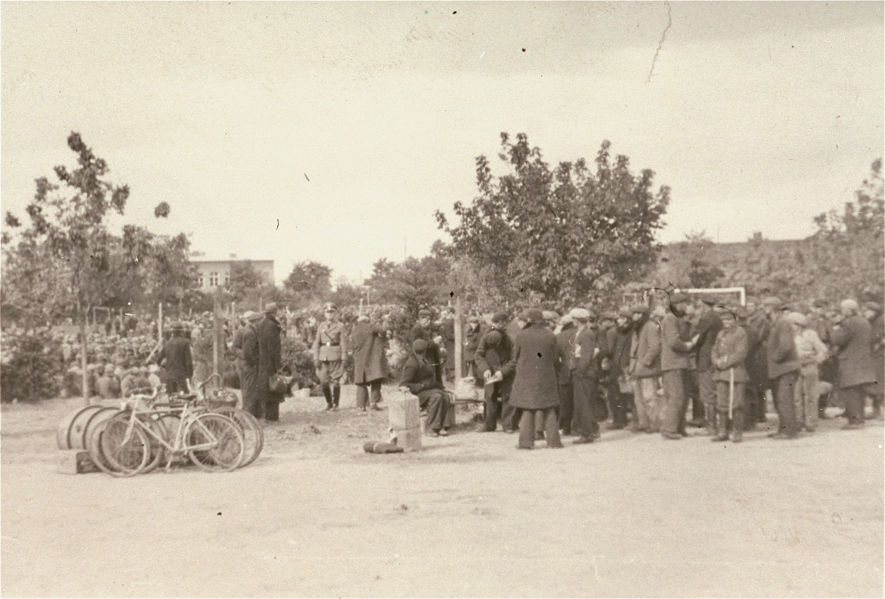 "[Probably, an SD officer walking among Polish and Jewish civilians interned in a temporary holding center.]  These prisoners may be what the Germans called ""Wehrfaehige"", or persons capable of carrying arms, who were summarily interned during and immediately after the Polish campaign as a security measure.   One of twenty-six images of Einsatzgruppen activities in Poland in 1939, found by Joseph Igra after the war, in a an album in an apartment in Sosnowiec."