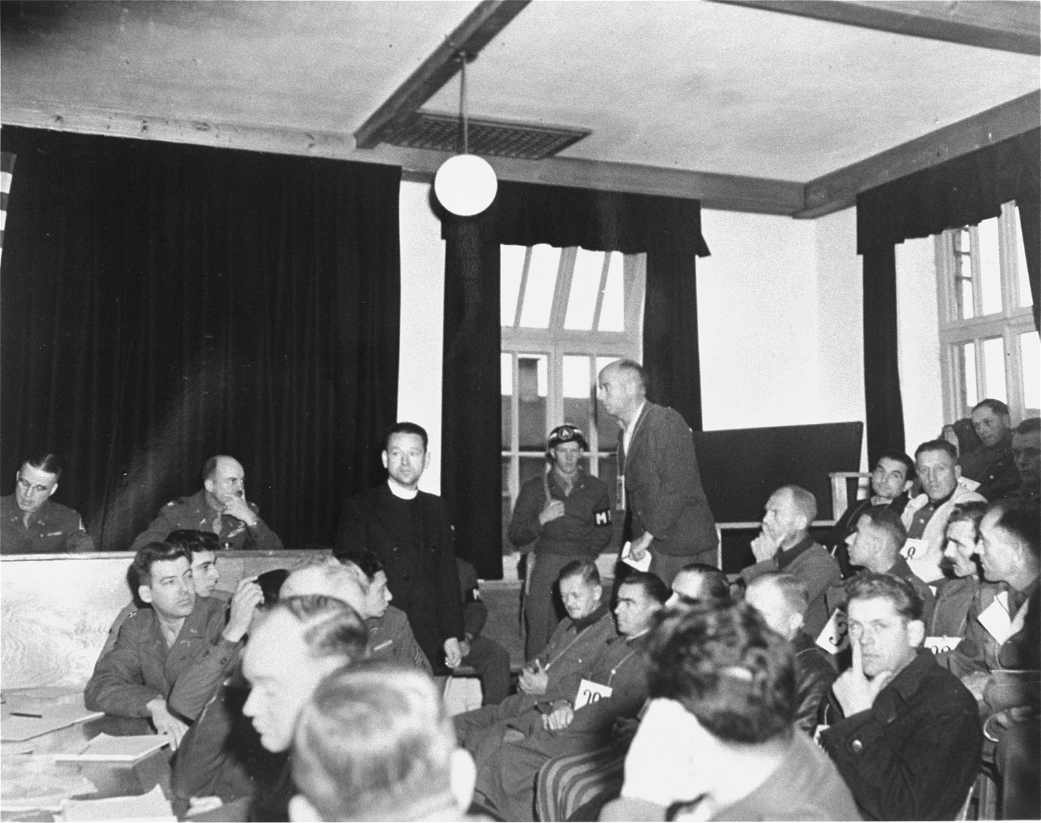 Defendant Fritz M. K. Becher answers the court's call to testify during the trial of former camp personnel and prisoners from Dachau.