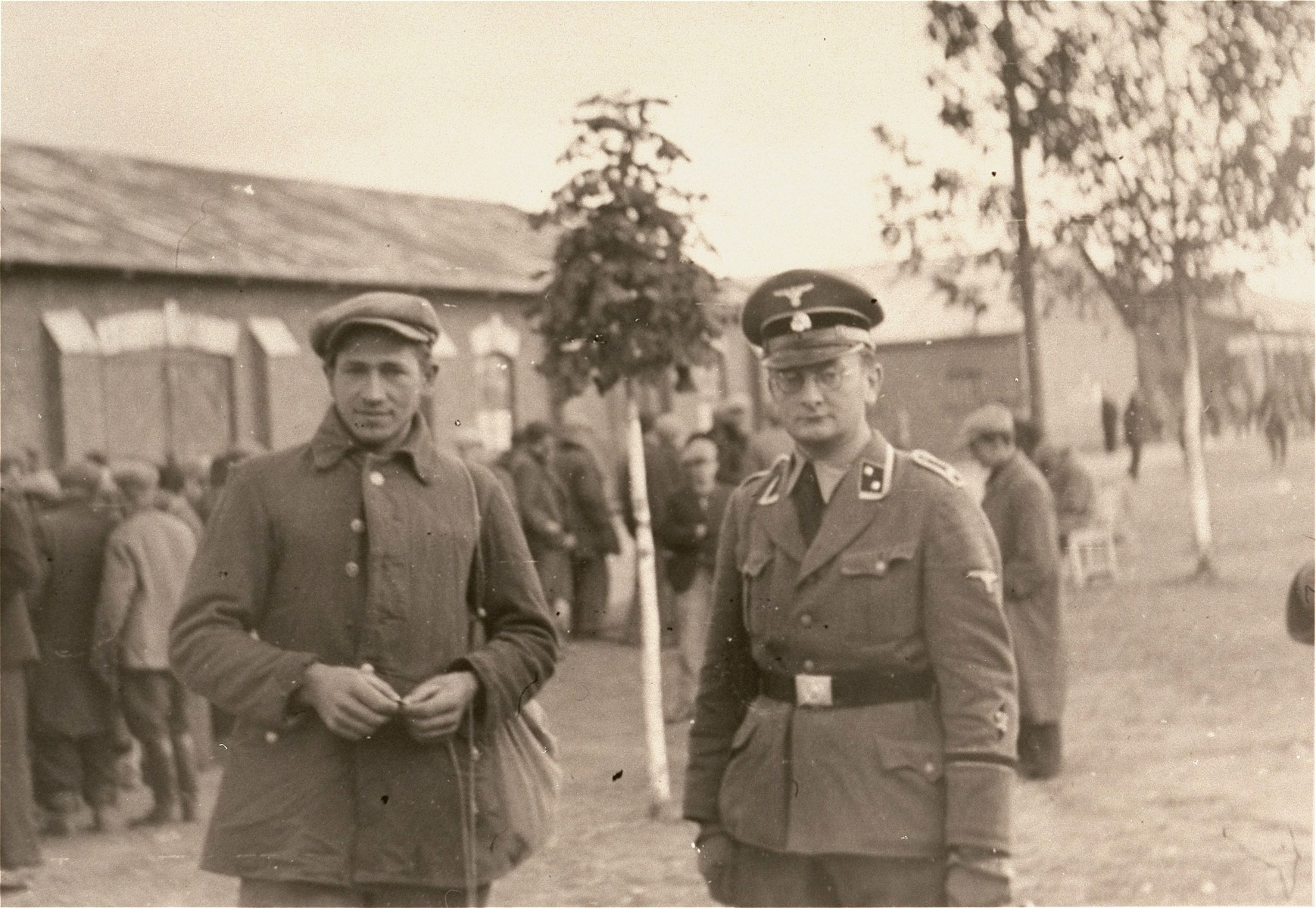 "An SD officer posing with a Pole who probably been detained for questioning.  This man and the others behind him could be what the Germans referred to as ""Wehrfaehige,"" or persons capable of carrying arms, who were summarily interned during and immediately after the Polish campaign as a security measure.   One of twenty-six images of Einsatzgruppen activities in Poland in 1939, found by Joseph Igra after the war, in a an album in an apartment in Sosnowiec."