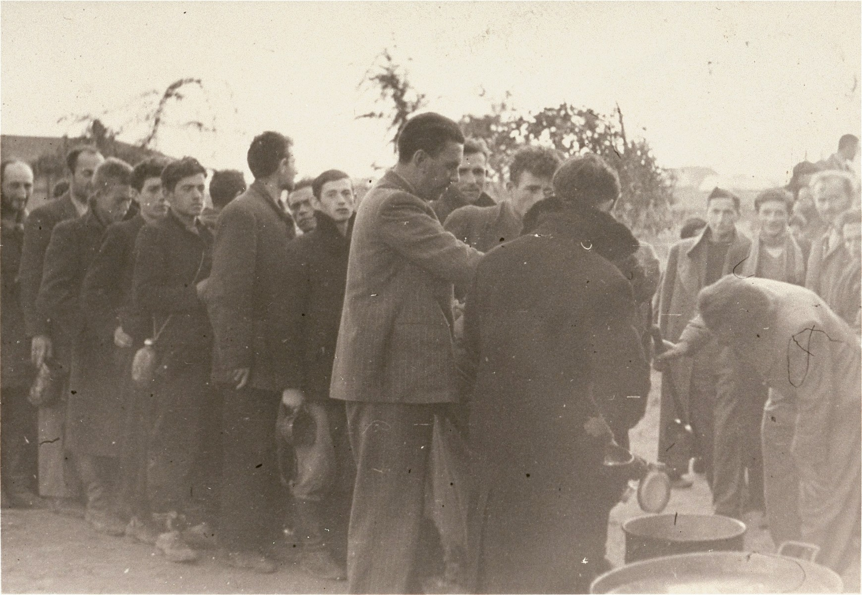 """[Probably, Polish and Jewish civilians interned by the SD in a temporary holding center lining up for food.]  These prisoners may be what the Germans called """"Wehrfaehige,"""" or persons capable of carrying arms, who were often summarily interned during and immediately after the Polish campaign as a security measure.   One of twenty-six images of Einsatzgruppen activities in Poland in 1939, found by Joseph Igra after the war, in a an album in an apartment in Sosnowiec."""