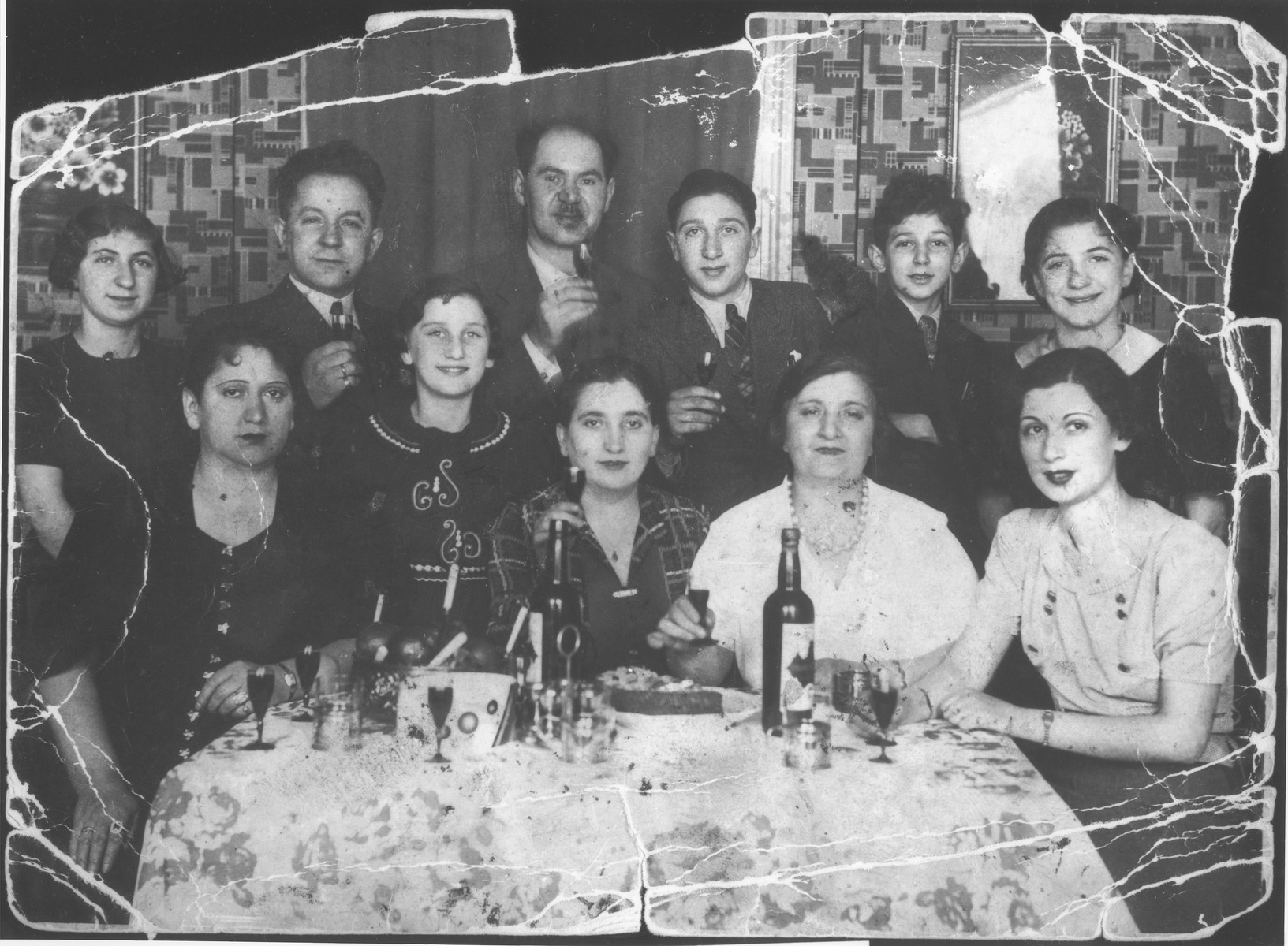 Members of the Edelstein family gather around a table holding liqueur glasses.  The Edelsteins moved to Amsterdam from Warsaw in the interwar period.