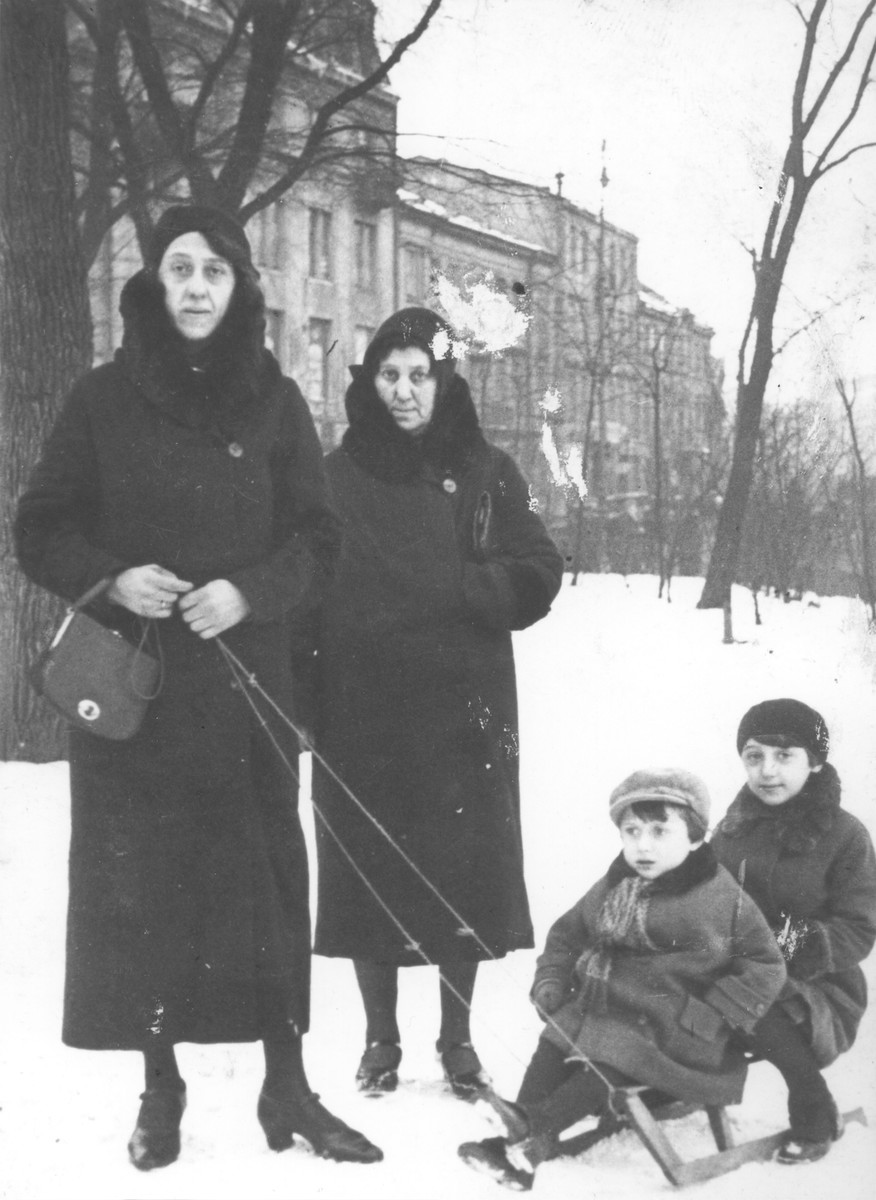 Two Jewish children are pulled on a sled in a Warsaw park by their mother and grandmother.  Pictured are Chaya Nortman (center), her daughter Dvora (left), and Dvora's two children.