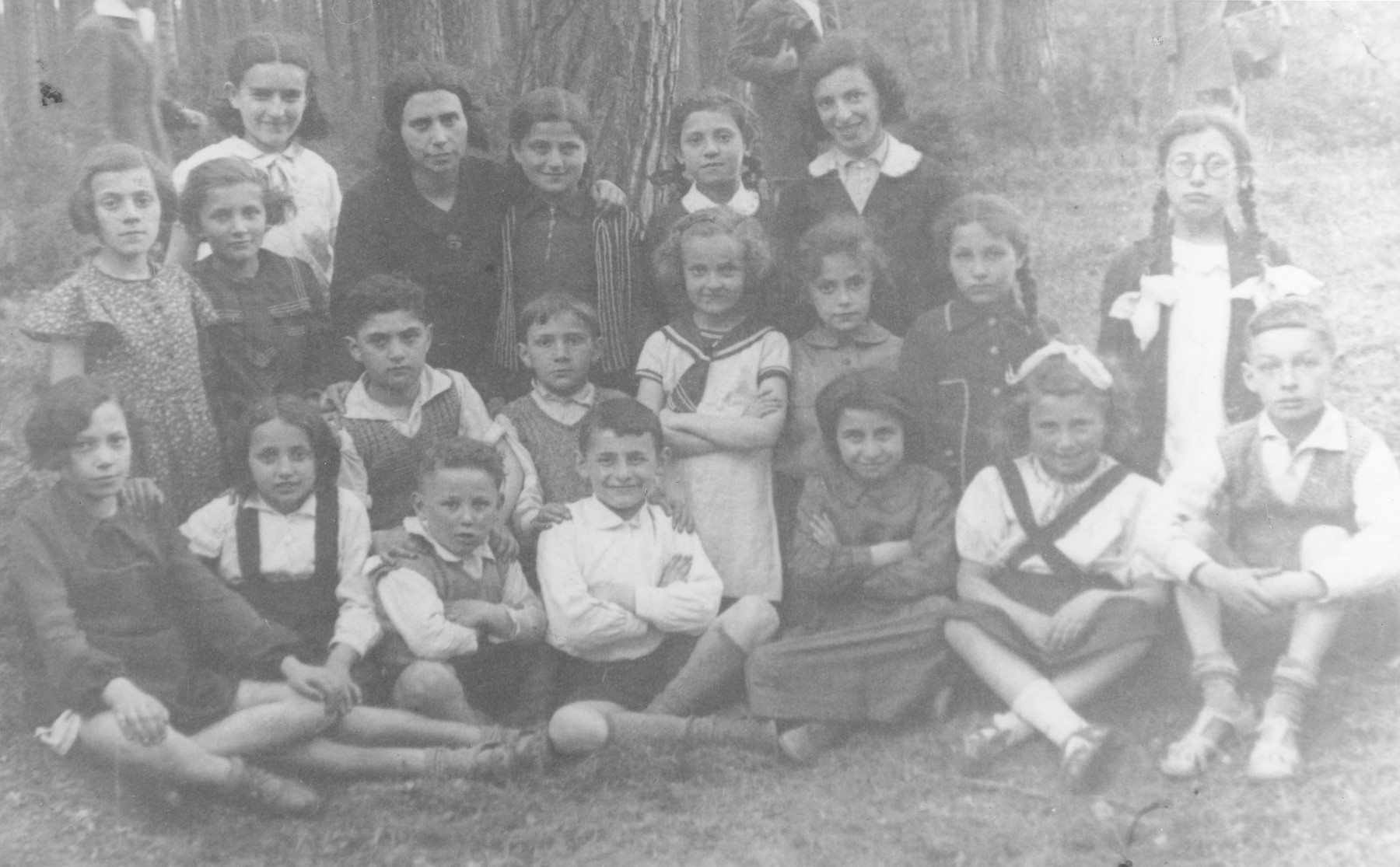 Group portrait of Jewish children from the Tarbut school in Ostrow Mazowiecka on an outing in the woods.  Among those pictured are the teacher Mrs. Shedletcka (top row, second from the left); her son, Aaron Rubinstein (front row, center); Chana Schwartz (front row, second from the right); Shimon Epstein (front row, first on the right); Lea Rubinstein (middle row, first on the left); Moniek Lichtenstein (middle row, third from the left); Miryam Galant (top row, third from the right); Moshe Friedman (middle row, center); and Tema Sosnowska (middle row, fourth from the right).