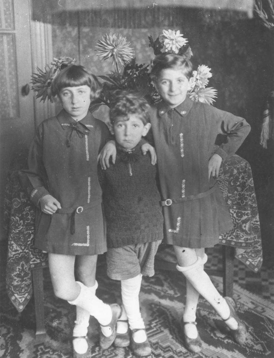 Studio portrait of the three Nortman children in Amsterdam.  Among those pictured are Adele Nortman (left) and Yankel Nortman (center).  During WWII Adele escaped from a deportation transport and was hidden by a German family.  She and her sister survived, but her brother, Yankel, perished in Auschwitz.