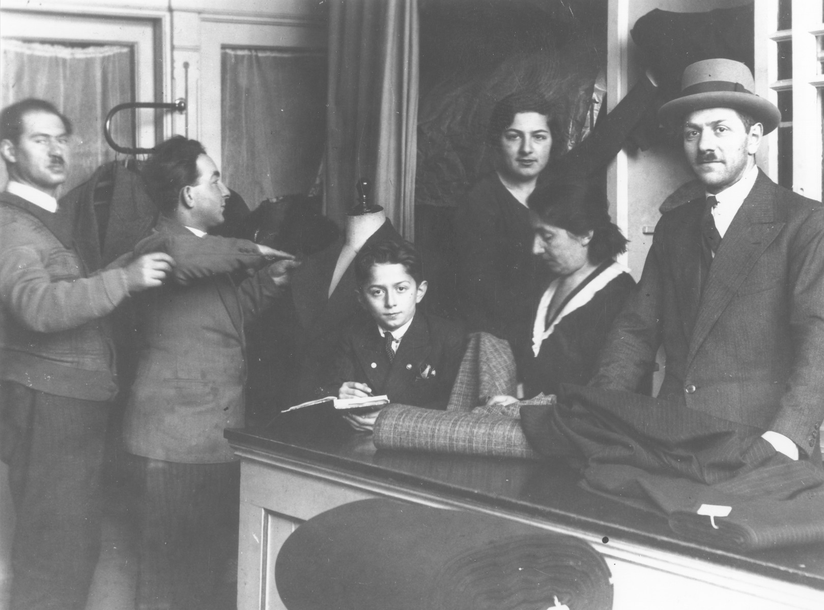A Jewish family works in a tailor shop in Amsterdam.  Among those pictured is Yankel Nortman (far left), who had moved to Amsterdam from Warsaw in 1932.  He later perished during the Holocaust.