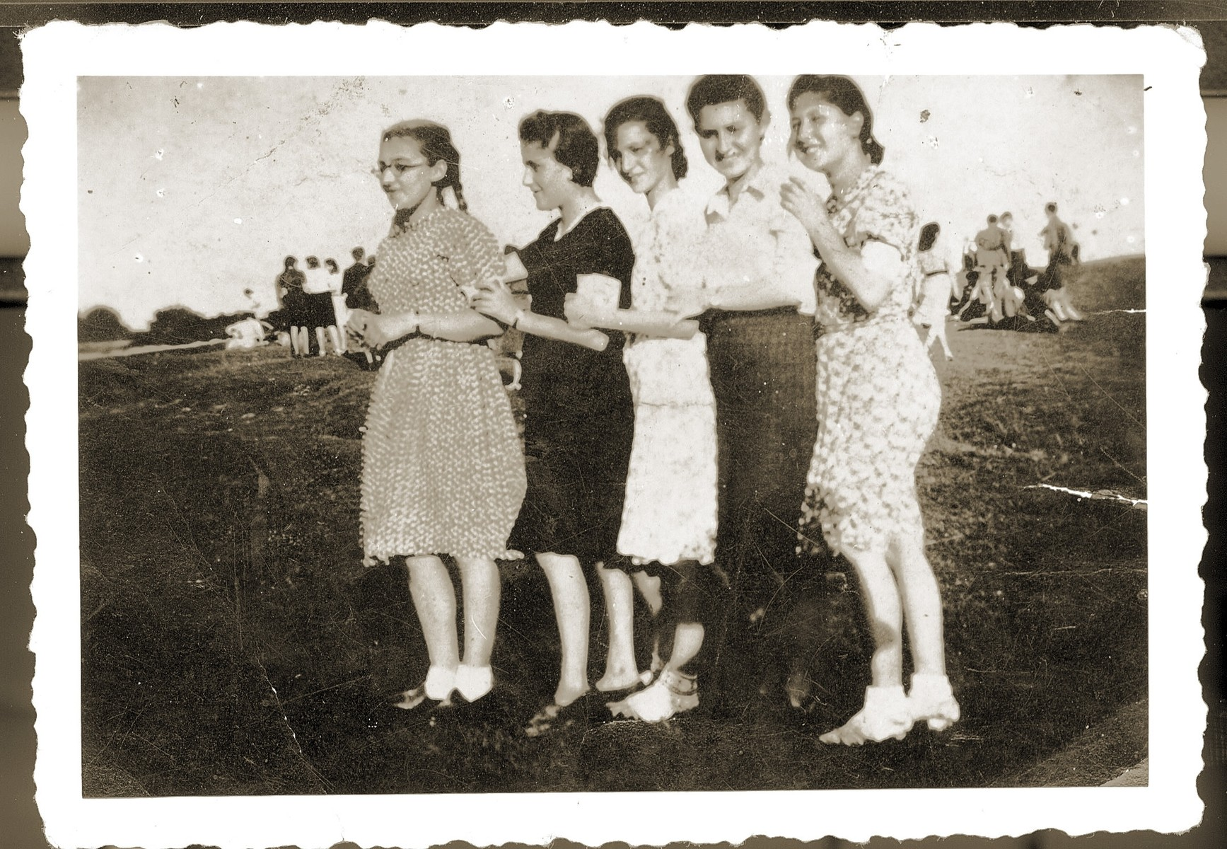 Five young women in the Bedzin ghetto pose in a line.    Pictured from left to right are Fela Zindorf, unidentified, Fredzia Gruengras, Regina Kuperberg, and Ala Lubliner.